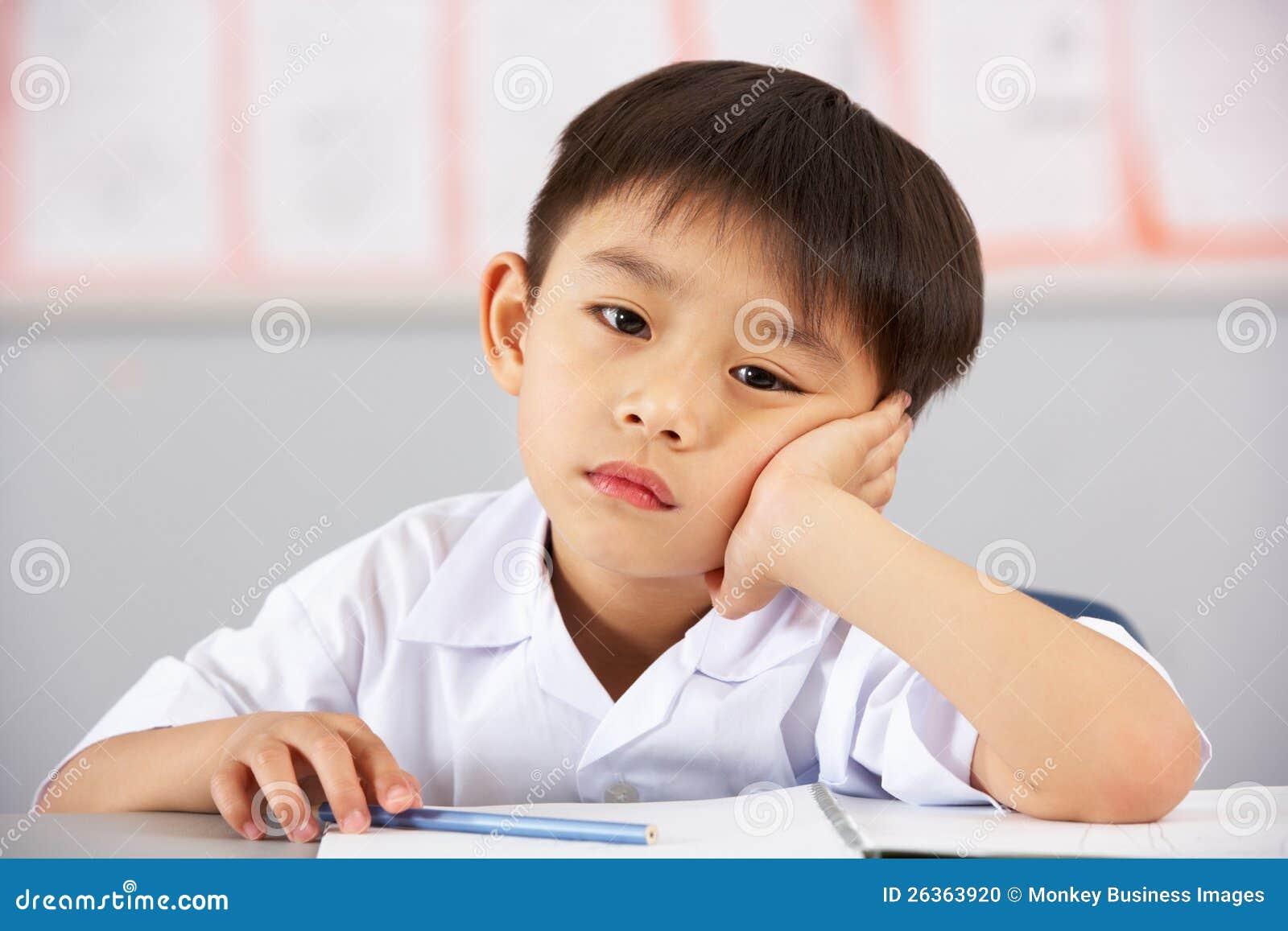 Olycklig Male deltagare som fungerar på skrivbordet i skola