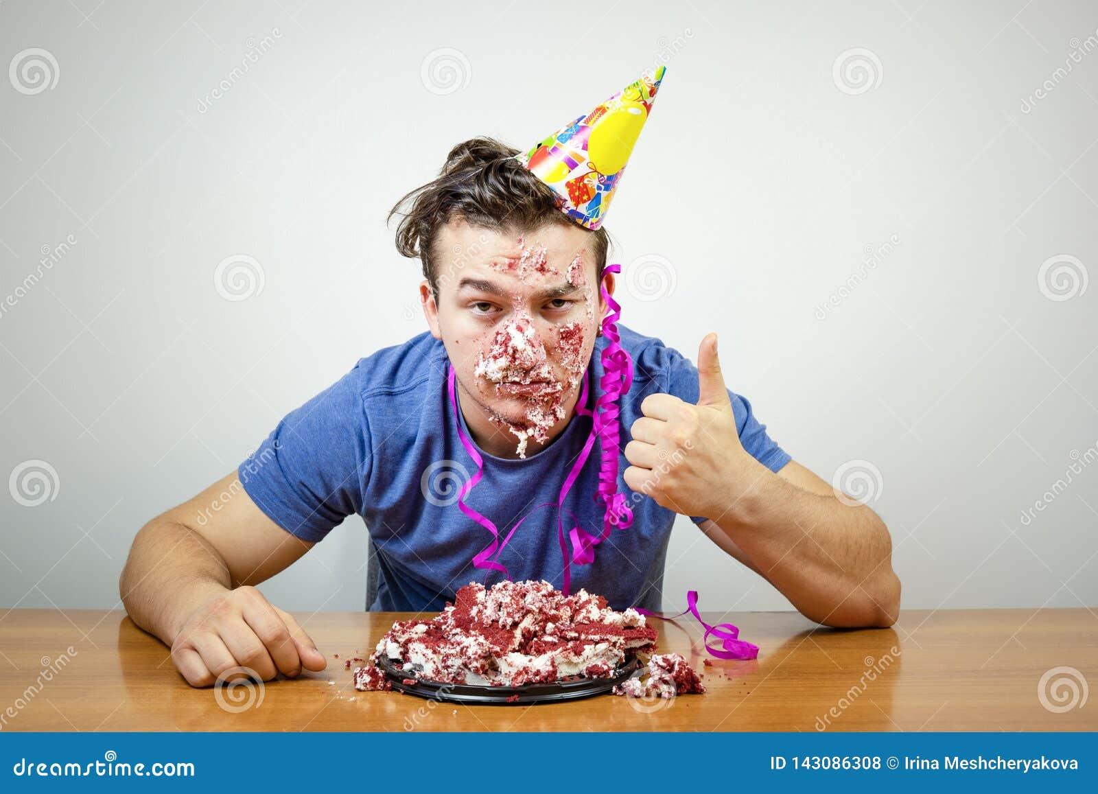 Olycklig snygg födelsedaggrabb för stående med kakan på framsidavisningtummen upp, olyckligt med överraskningpartiet att vänner s