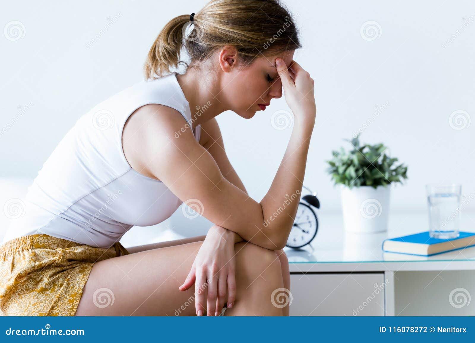Olyckligt ensamt deprimerat sammanträde för ung kvinna på säng hemma Fördjupningsbegrepp