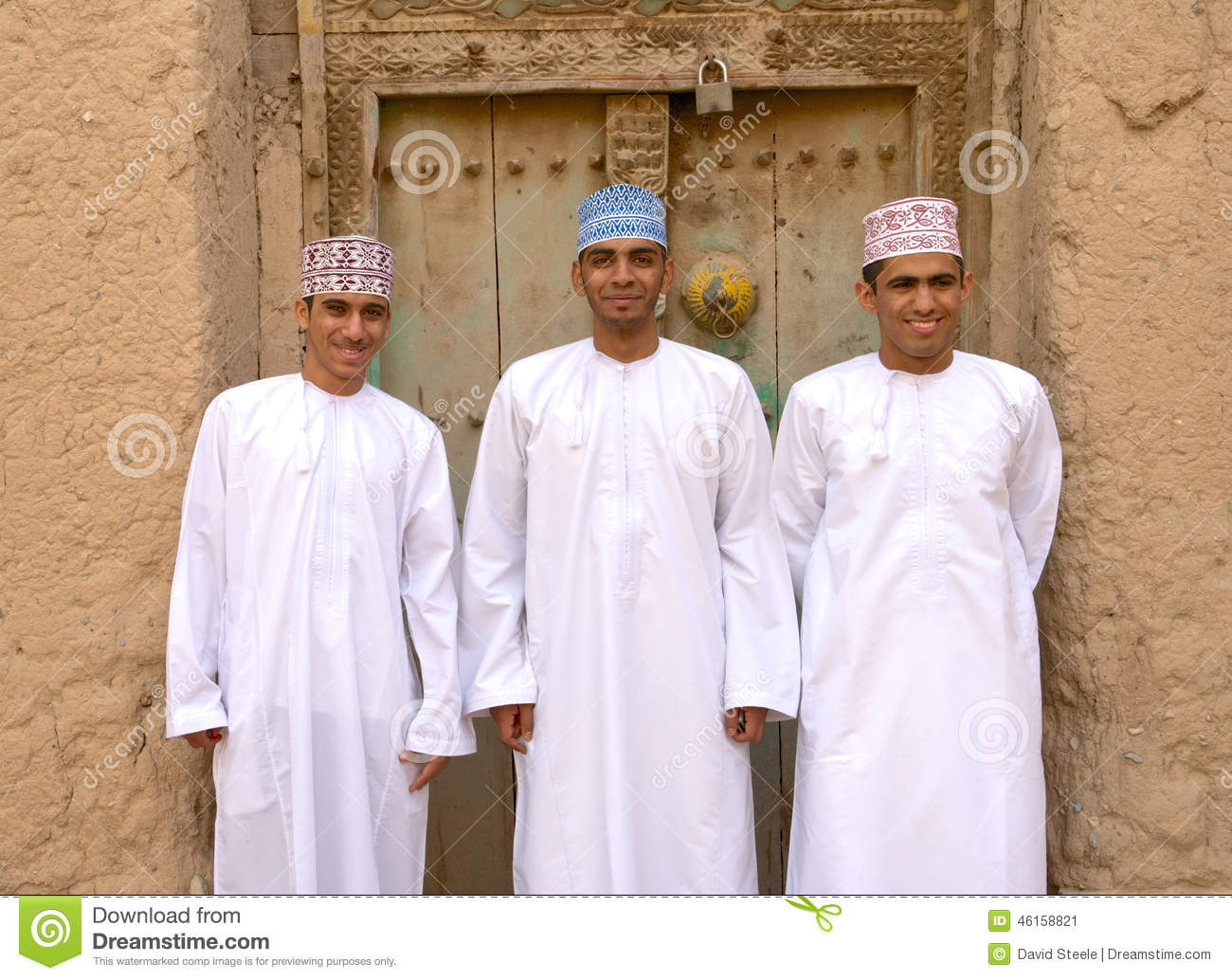 Three young Omani men in traditional dress at the ruins of Birkat Al ...