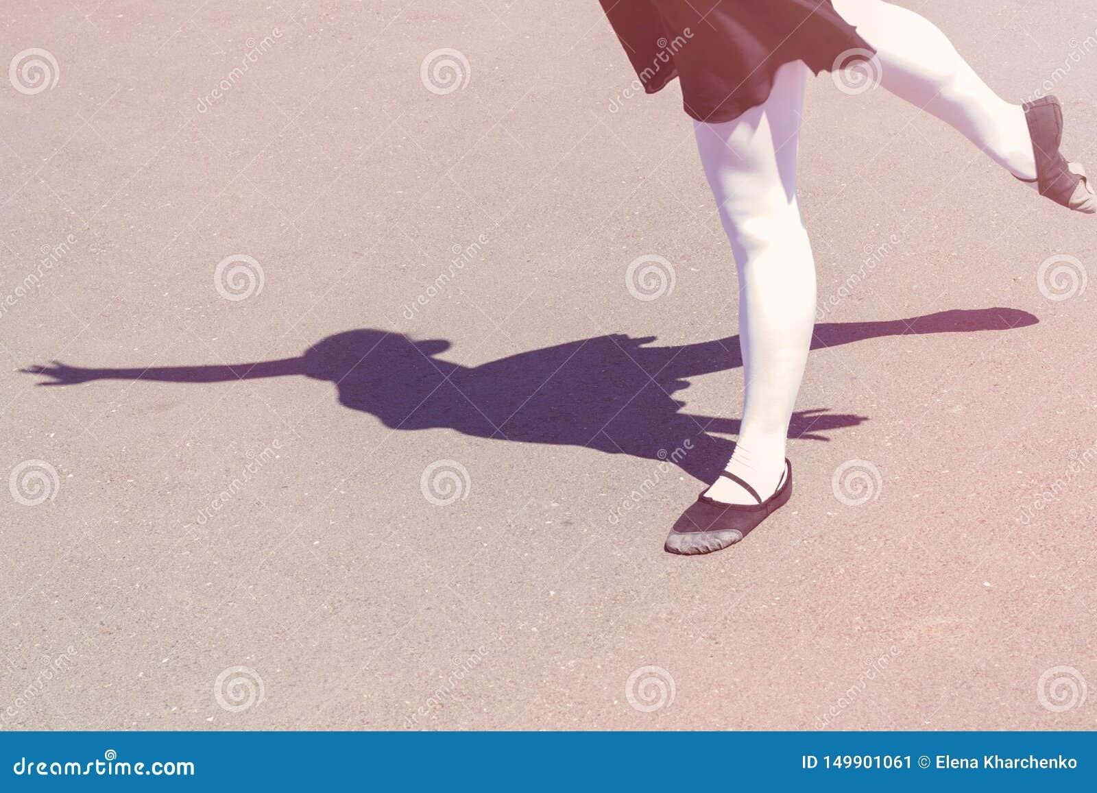 Ombre de la fille de danseur qui entreprend des démarches de danse dans un maillot de bain pour des chaussures de danse et de bal