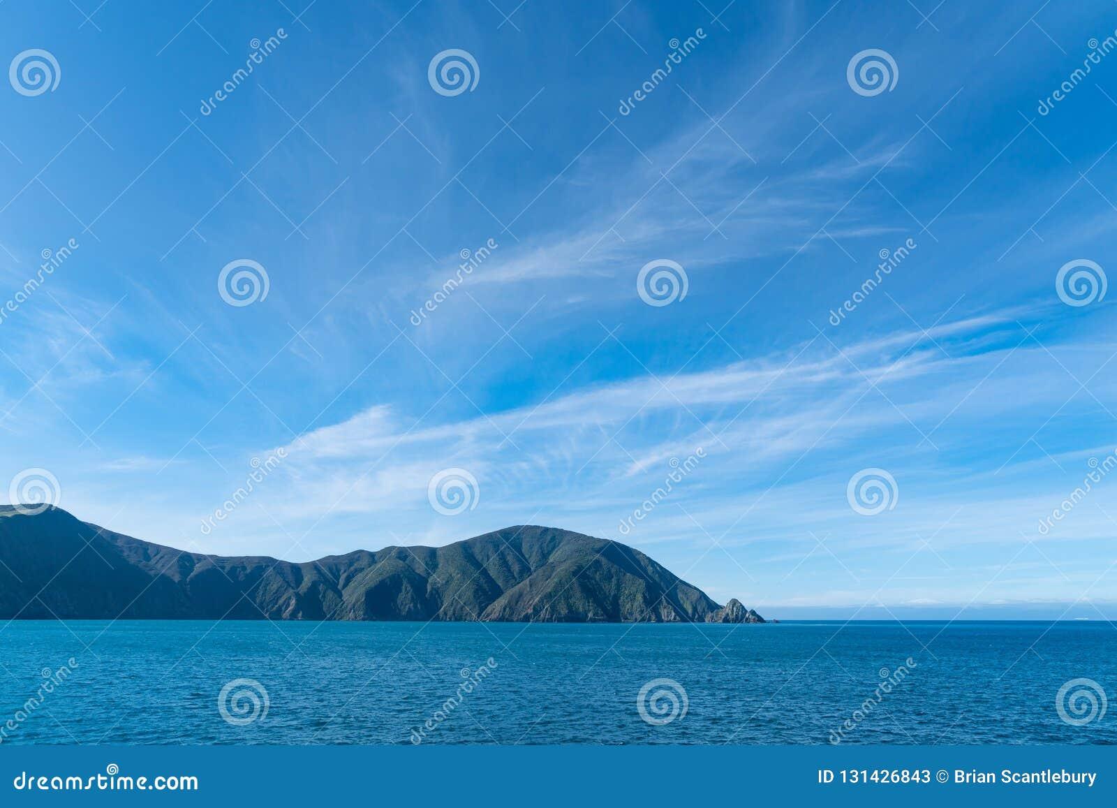 Ombre sulle colline sotto cielo blu con la regina entrante Charlotte Sound della nuvola esile leggera
