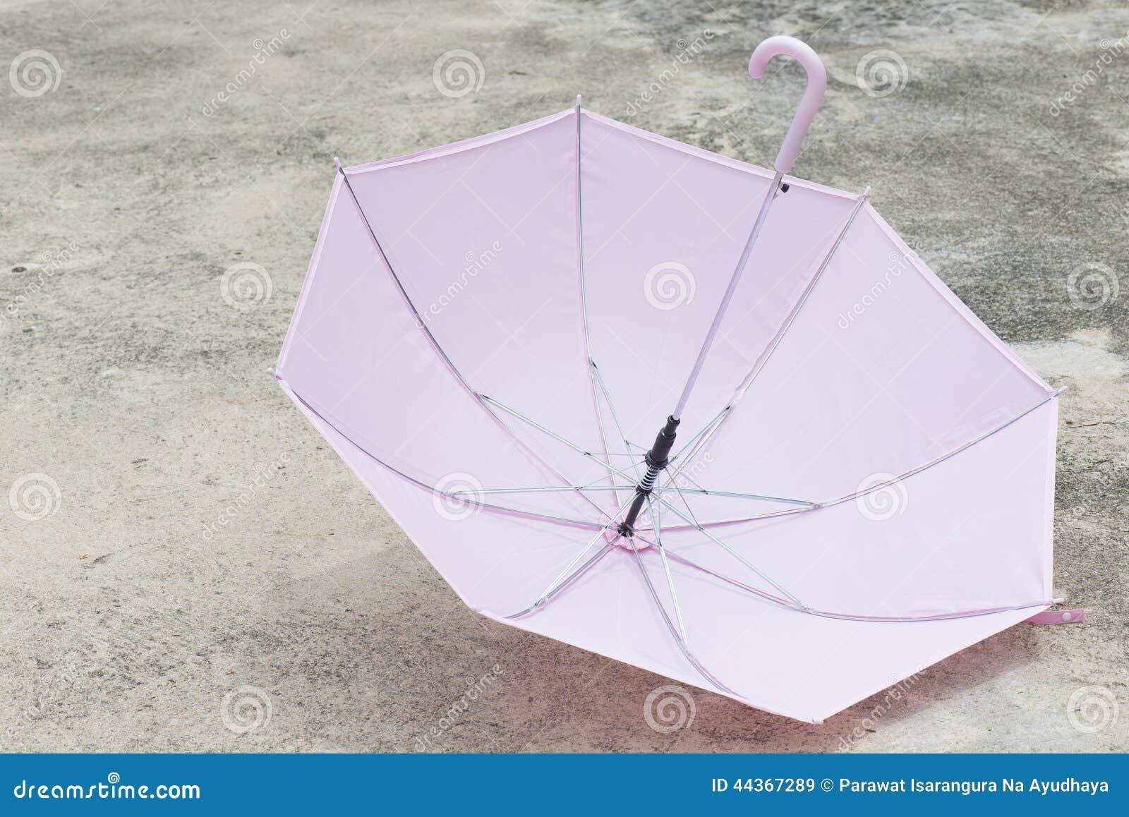 Ombrello rosa all aperto sul pavimento di calcestruzzo