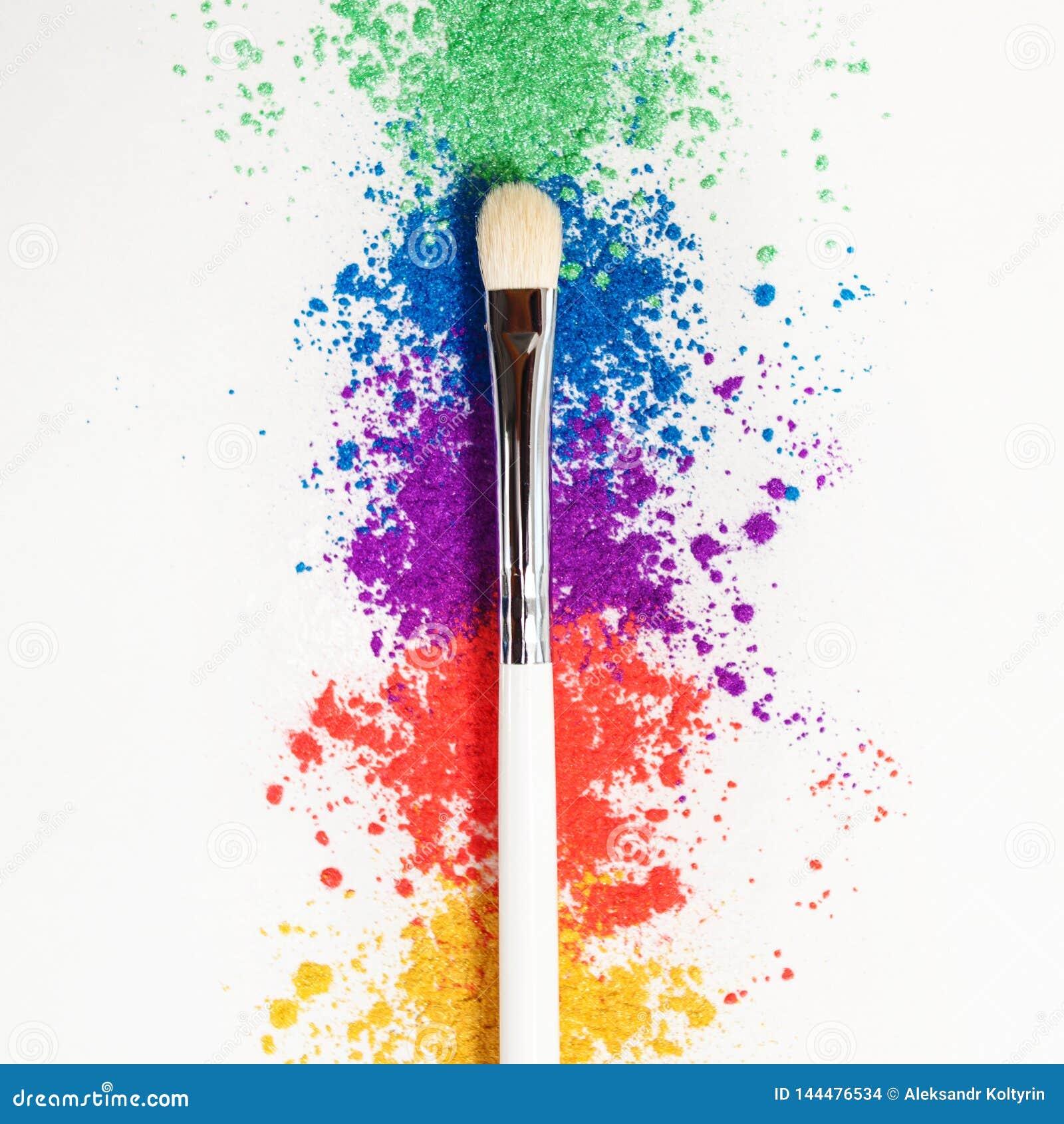 Ombretti luminosi nei colori differenti dell arcobaleno e delle spazzole per i cosmetici su un fondo bianco
