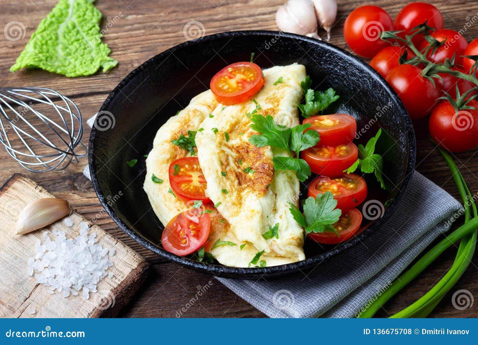 Omeleta com tomates de cereja e salsa verde fresca em uma bandeja preta do ferro
