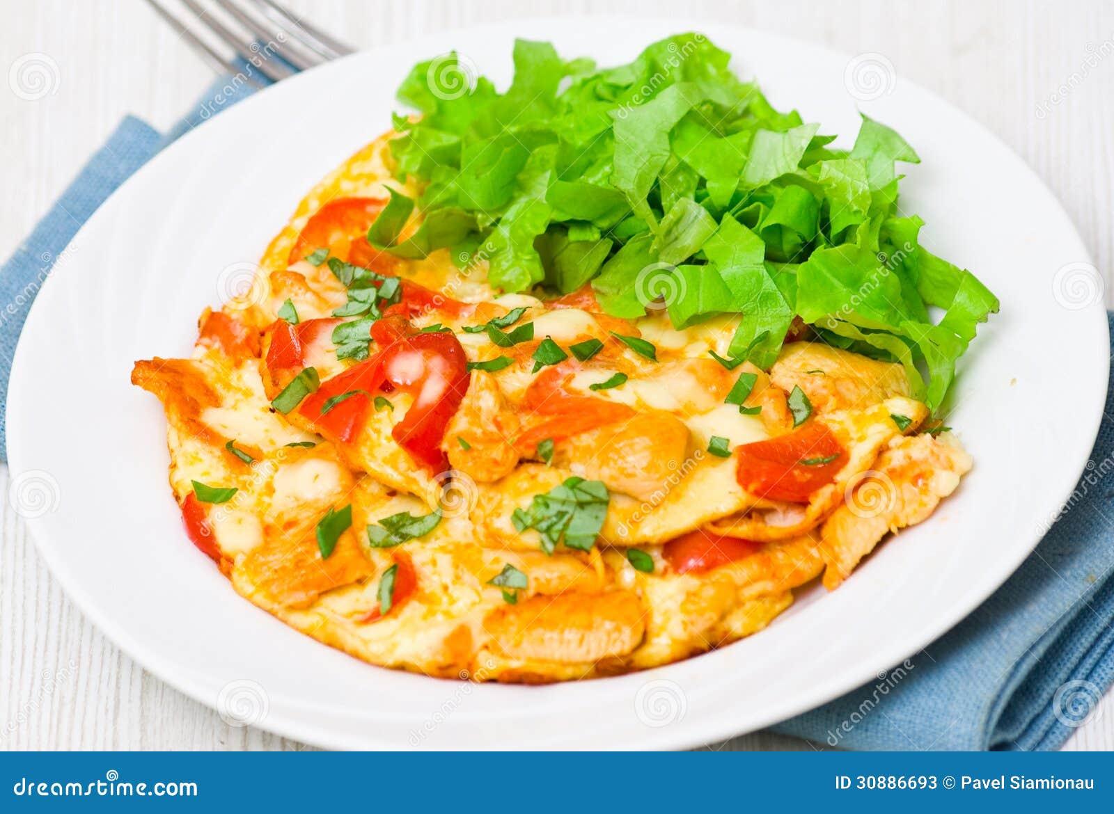 Omelett mit Scheiben der Hühnerbrust und des Gemüses