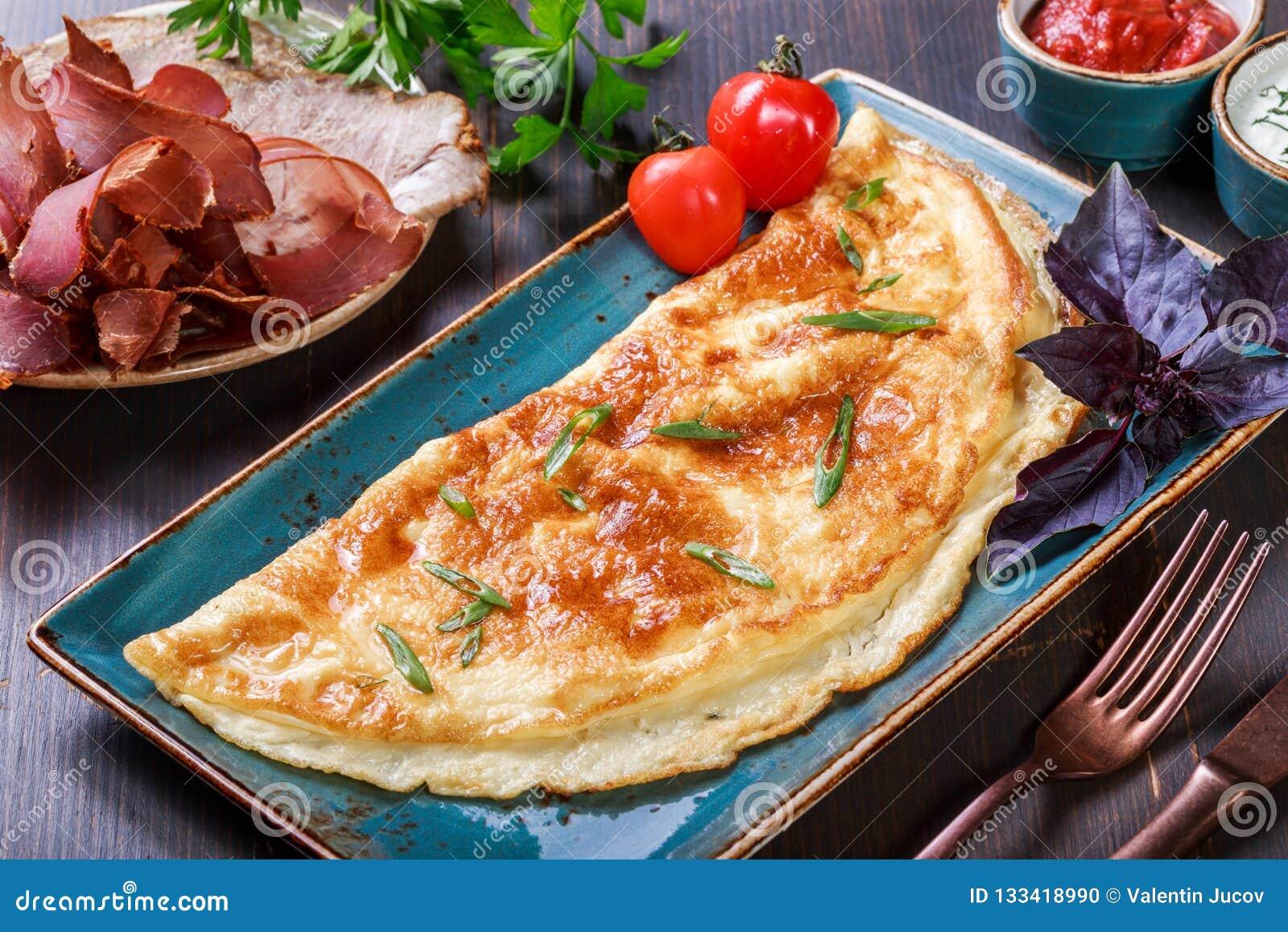 Omelette avec la sauce de prosciutto, de tranches jambon, de champignons, de verts, de fromage et tomate sur le fond en bois fonc