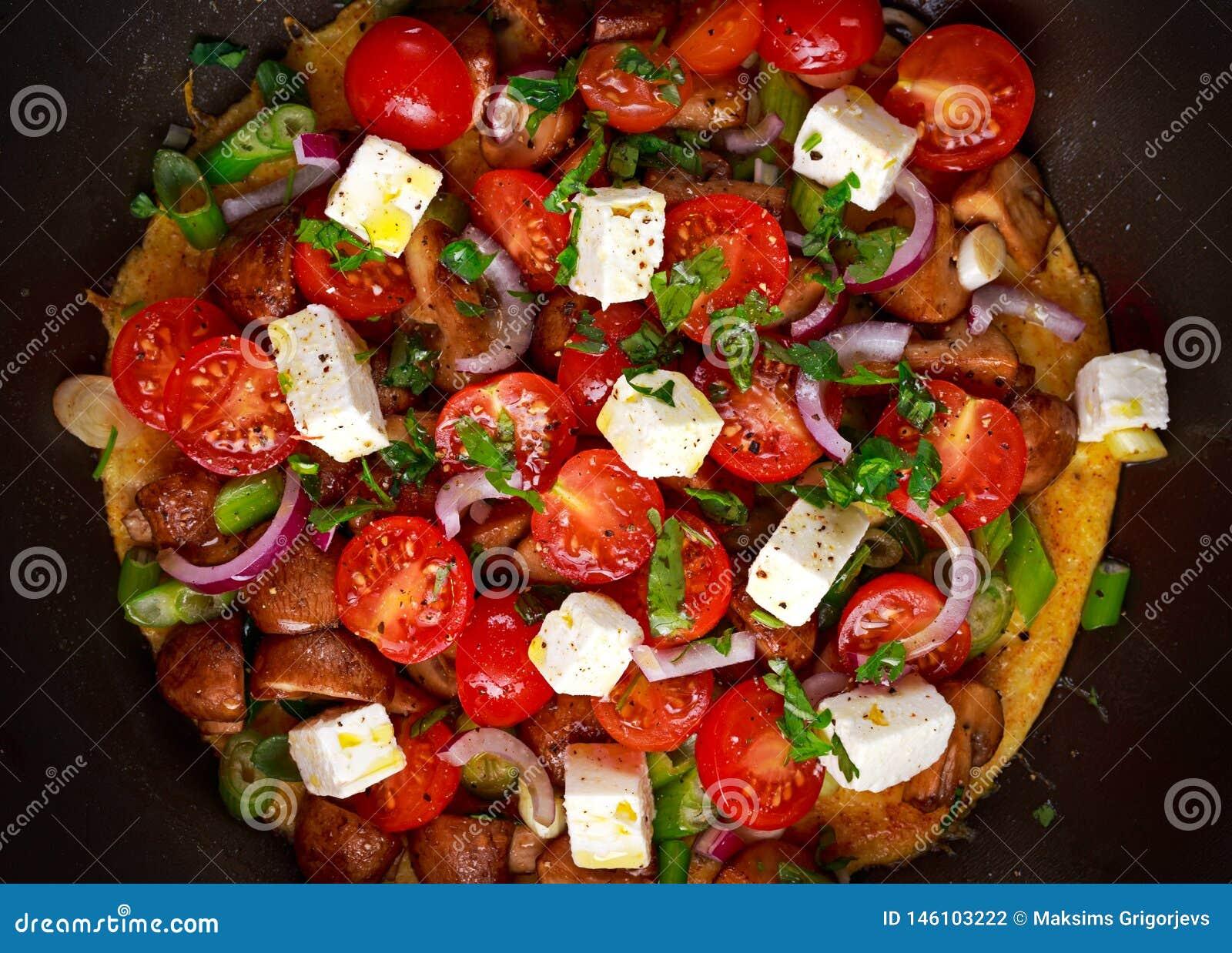 Omelette méditerranéenne de style dans la poêle avec du feta, des tomates-cerises, des oignons rouges, des champignons, des oigno