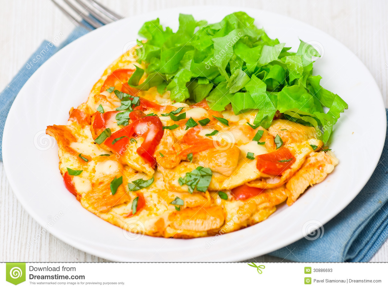 Omelette with slices of chicken breast and vegetables