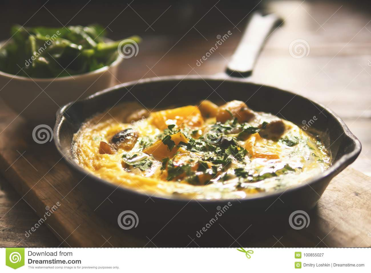 Omelette with Vegetables in Old Vintage Iron Frying Pan on Wooden Table. Autumn Vegetarian Breakfast.