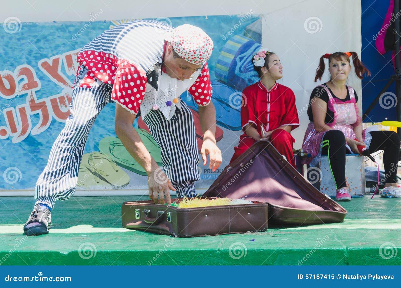 Omer (cerveja-Sheva), ISRAEL - homem - clown com uma mala de viagem marrom velha na fase verde do verão e nos dois assistentes, o