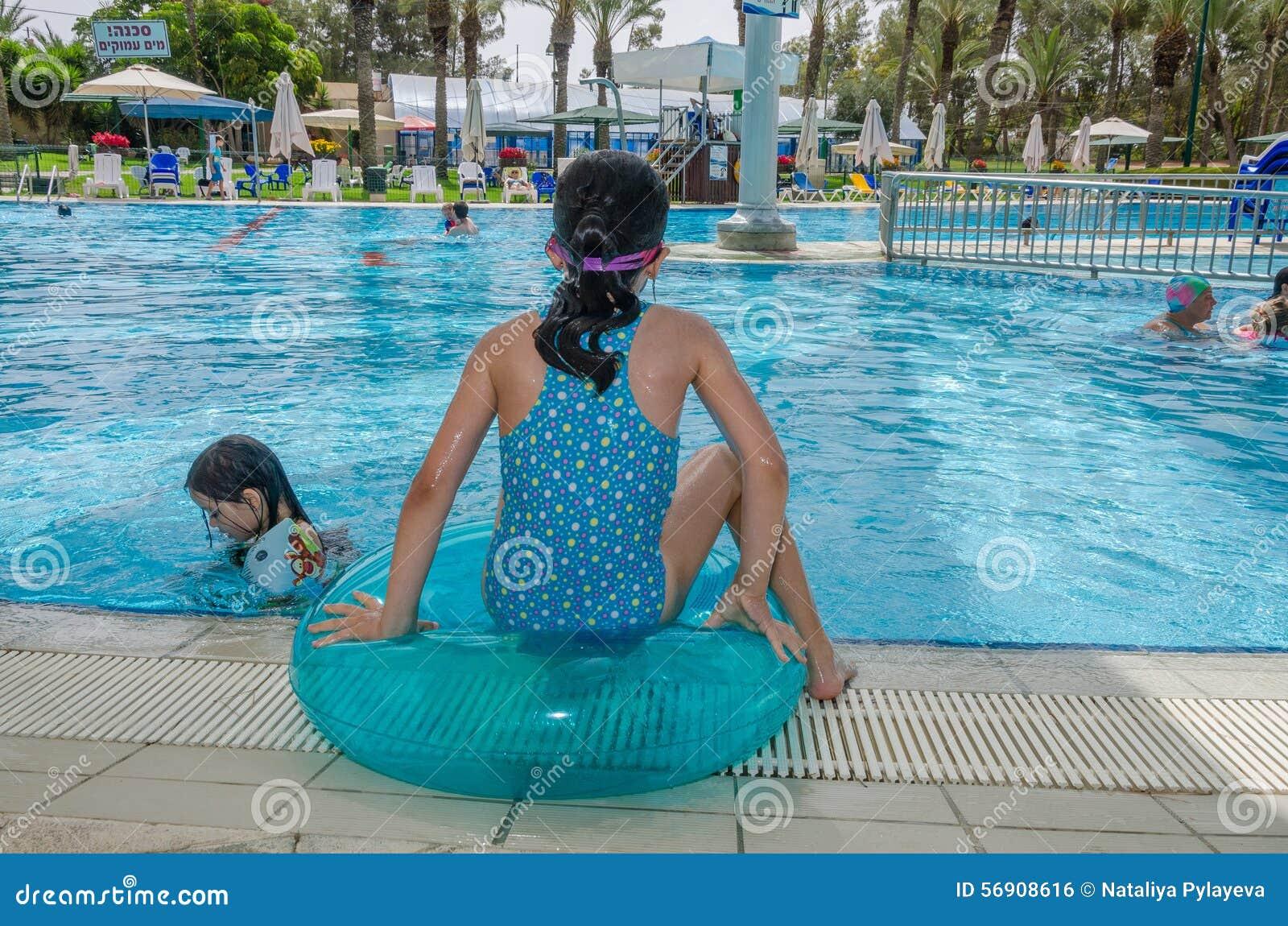 Omer, Negev, ΙΣΡΑΗΛ - 27 Ιουνίου, συνεδρίαση κοριτσιών στη διογκώσιμη πλάτη δαχτυλιδιών, που εξετάζει το νερό στη λίμνη Omer, Neg
