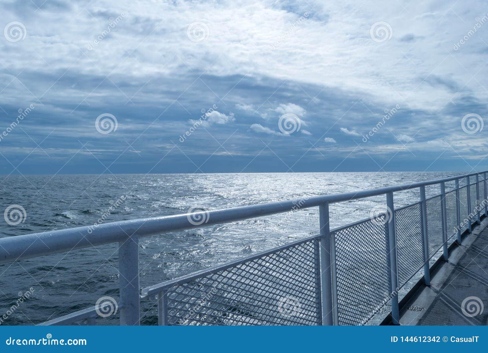 Omheinend op het hogere dek van een schip, dat met de horizon en de overweldigende blauwe hemel in de afstand samenkomt