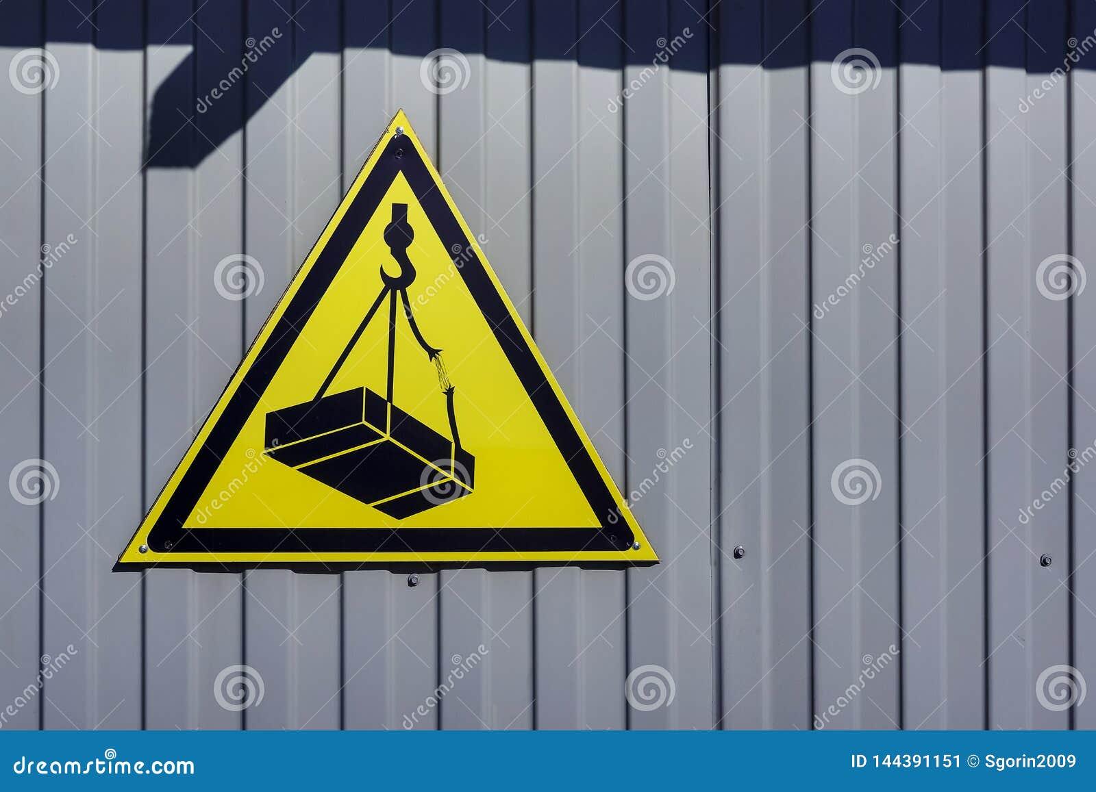 Omheiningsachtergrond met waarschuwingsbord over gevaar van dalende lading van kraan