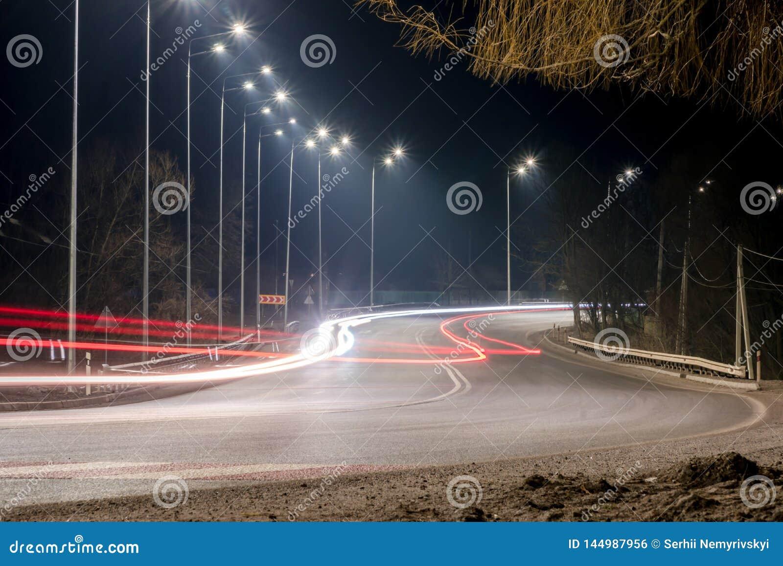 Γρήγορα κινούμενη κυκλοφορία τη νύχτα χειμερινή εποχή έννοια του δρόμου, της αφαίρεσης χιονιού και πάγου, του κινδύνου και της ασ