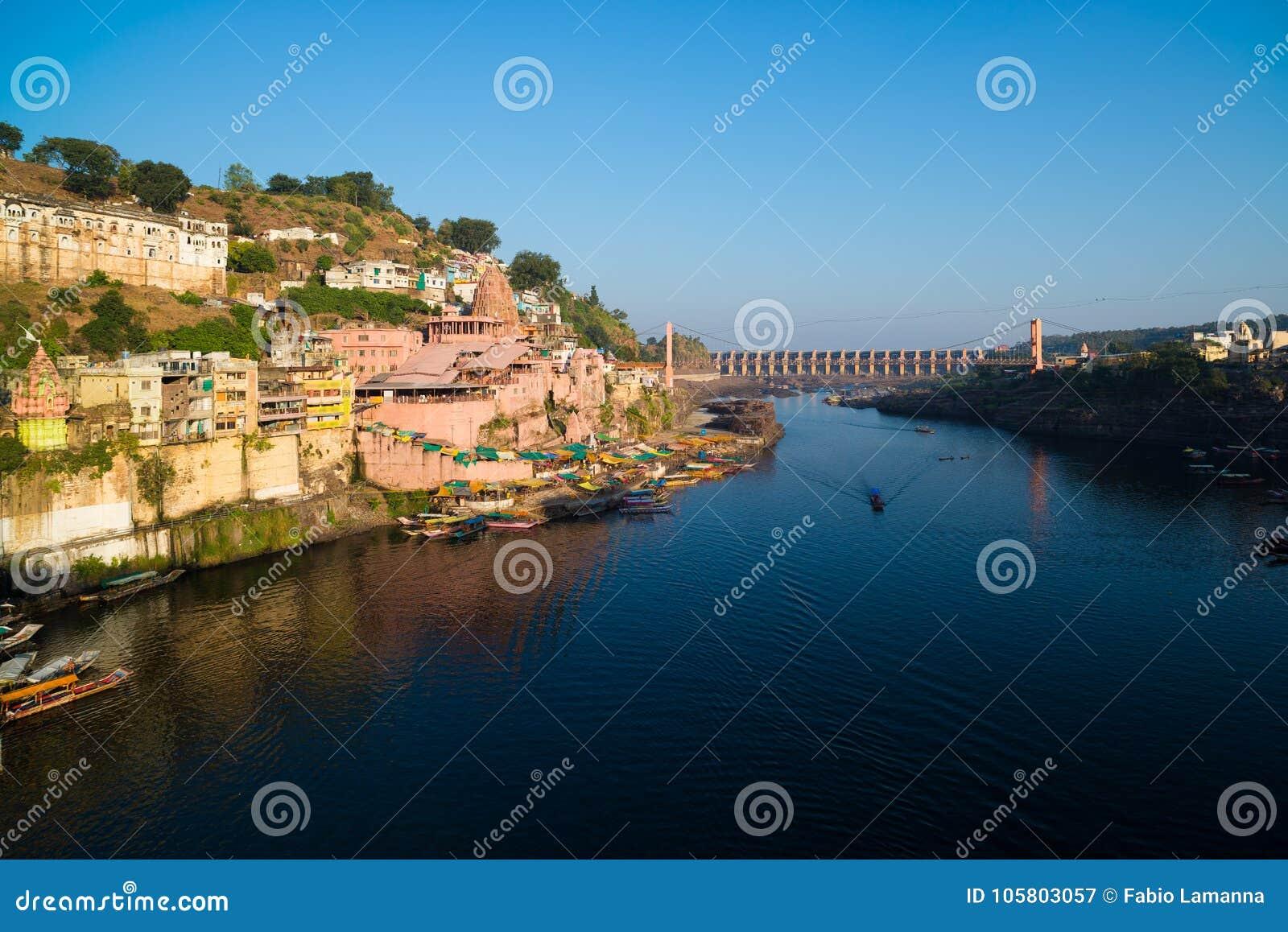 Omkareshwar cityscape, India, sacred hindu temple. Holy Narmada River, boats floating. Travel destination for tourists and pilgrim