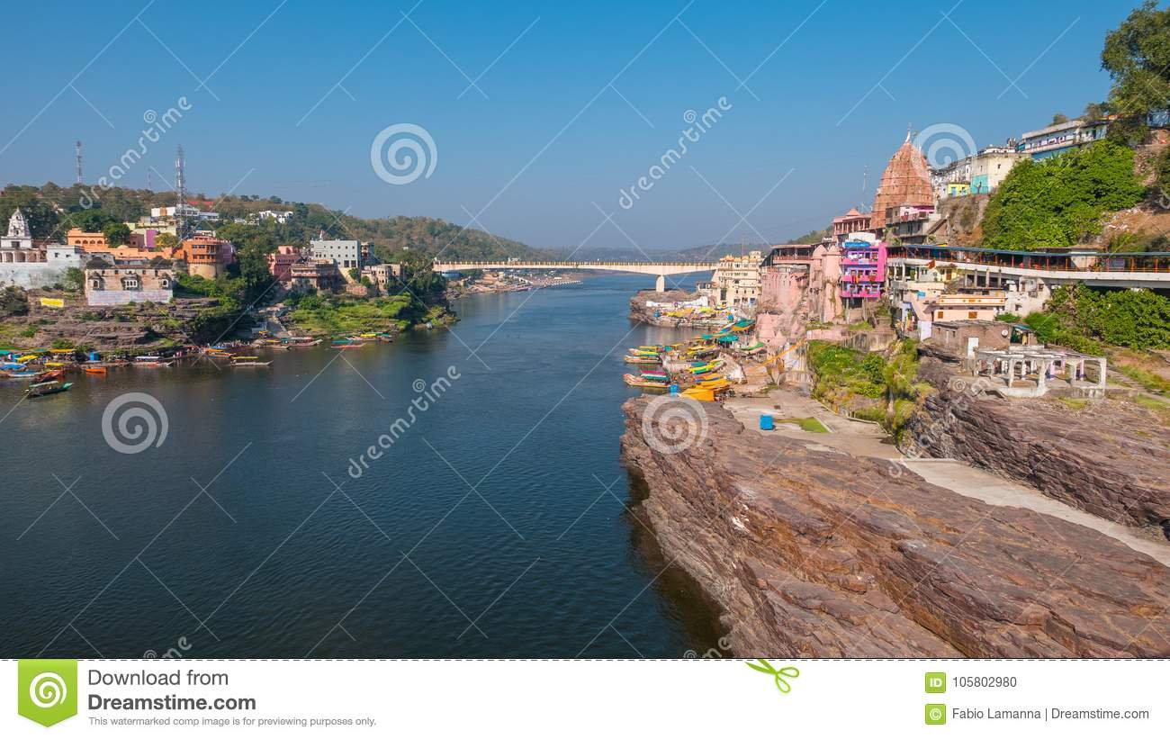 Omkareshwar cityscape, India, sacred hindu temple. Holy Narmada River, boats floating. Travel destination for tourists and pilgrim