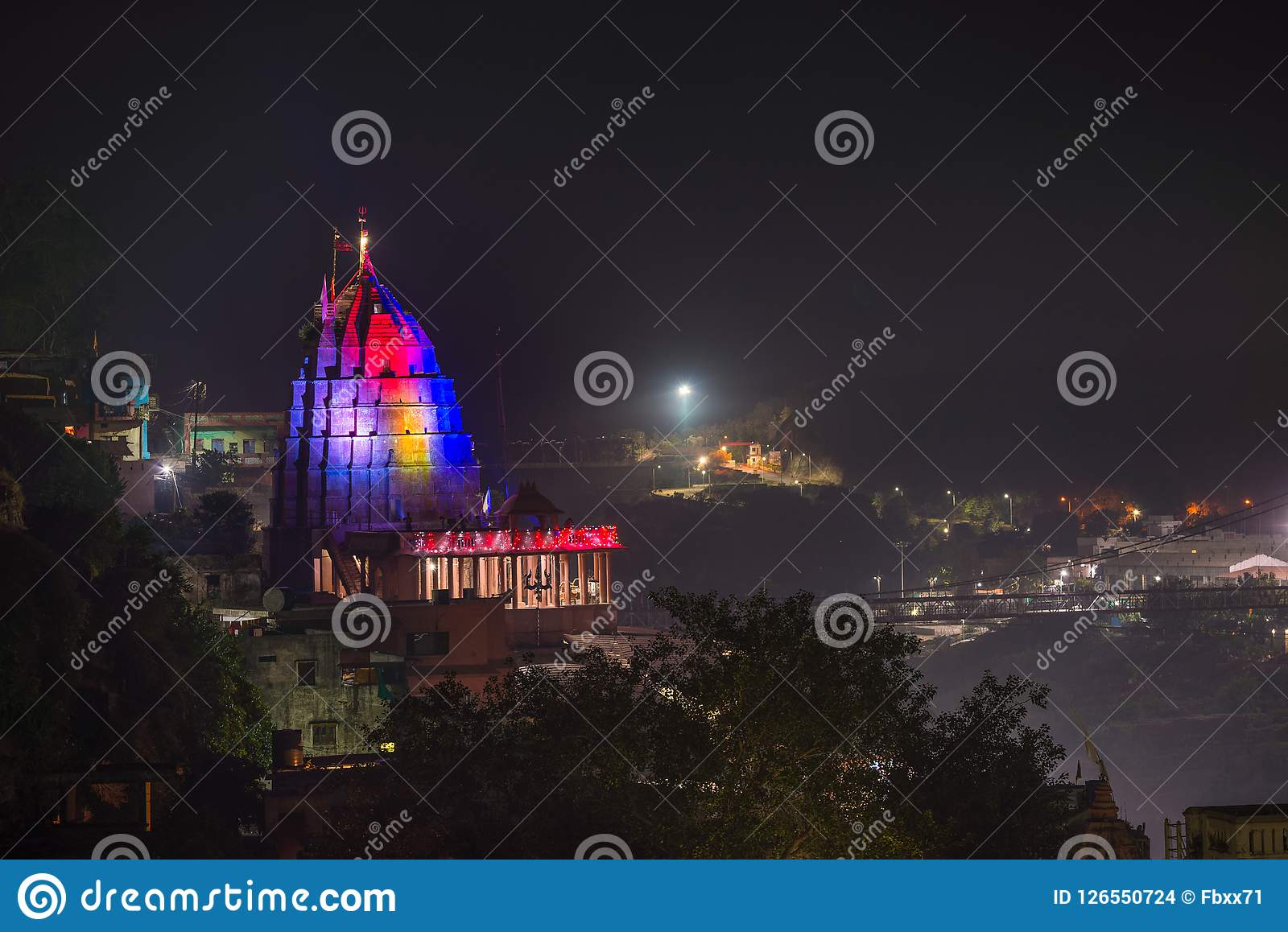 Omkareshwar cityscape by night, India, sacred hindu temple illuminated. Travel destination for tourists and pilgrims