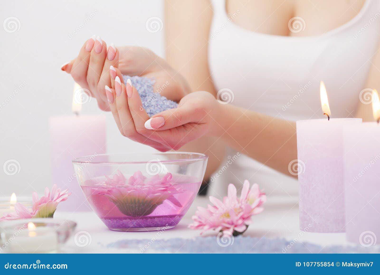 Omsorgsbomullsfingernailen spikar att ta bort swabfernissa Closeupen av härliga kvinnahänder med naturligt spikar I