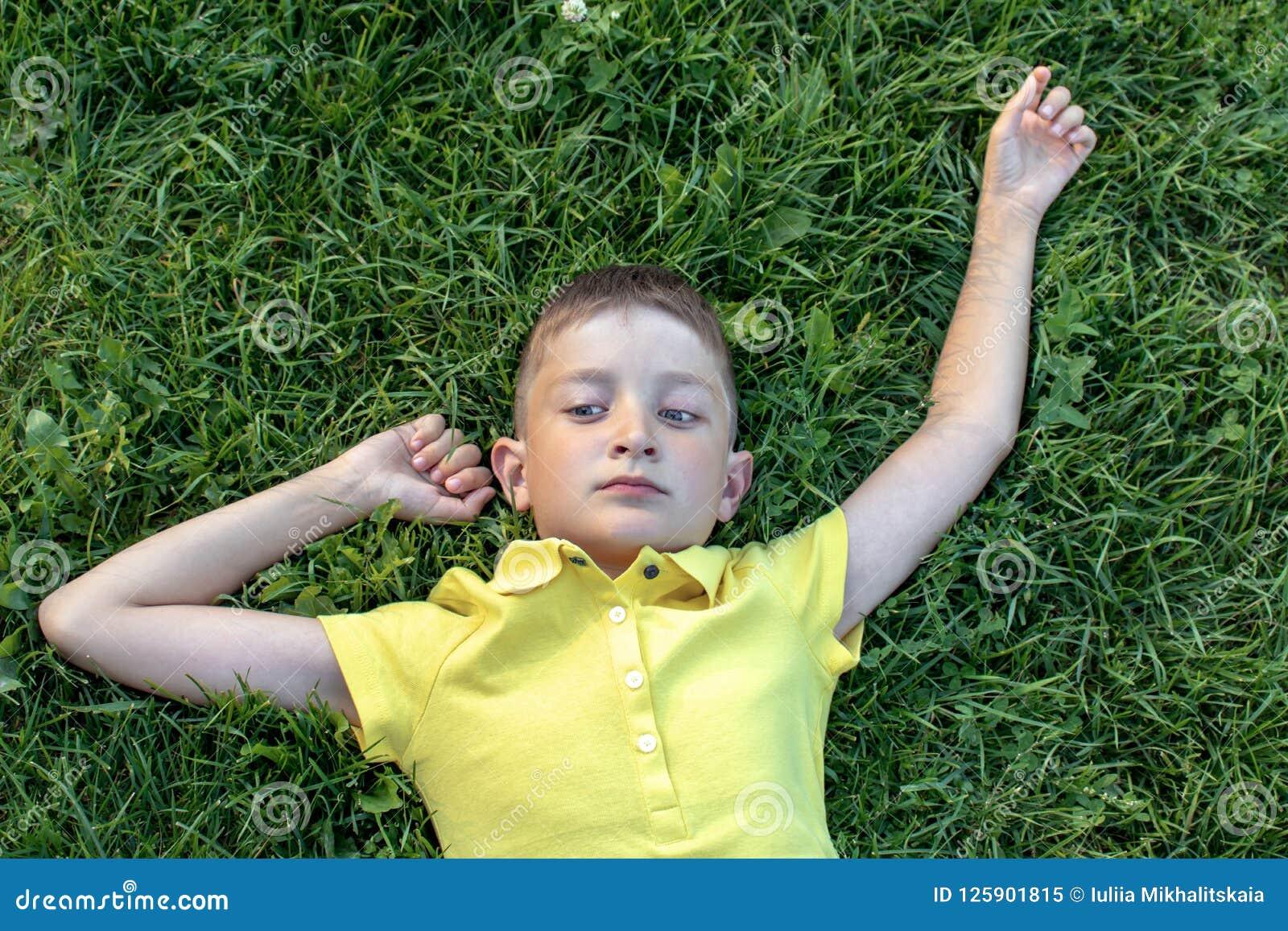 Onbezorgde Kaukasische jongen in geel overhemd die op het gras liggen