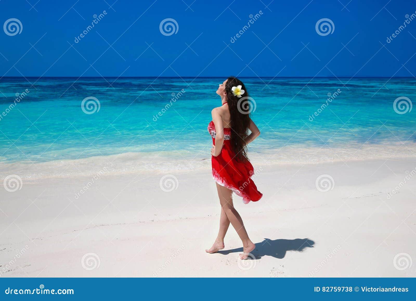 Onbezorgde mooie vrouw die op het exotische overzees genieten van Gelukkige brune