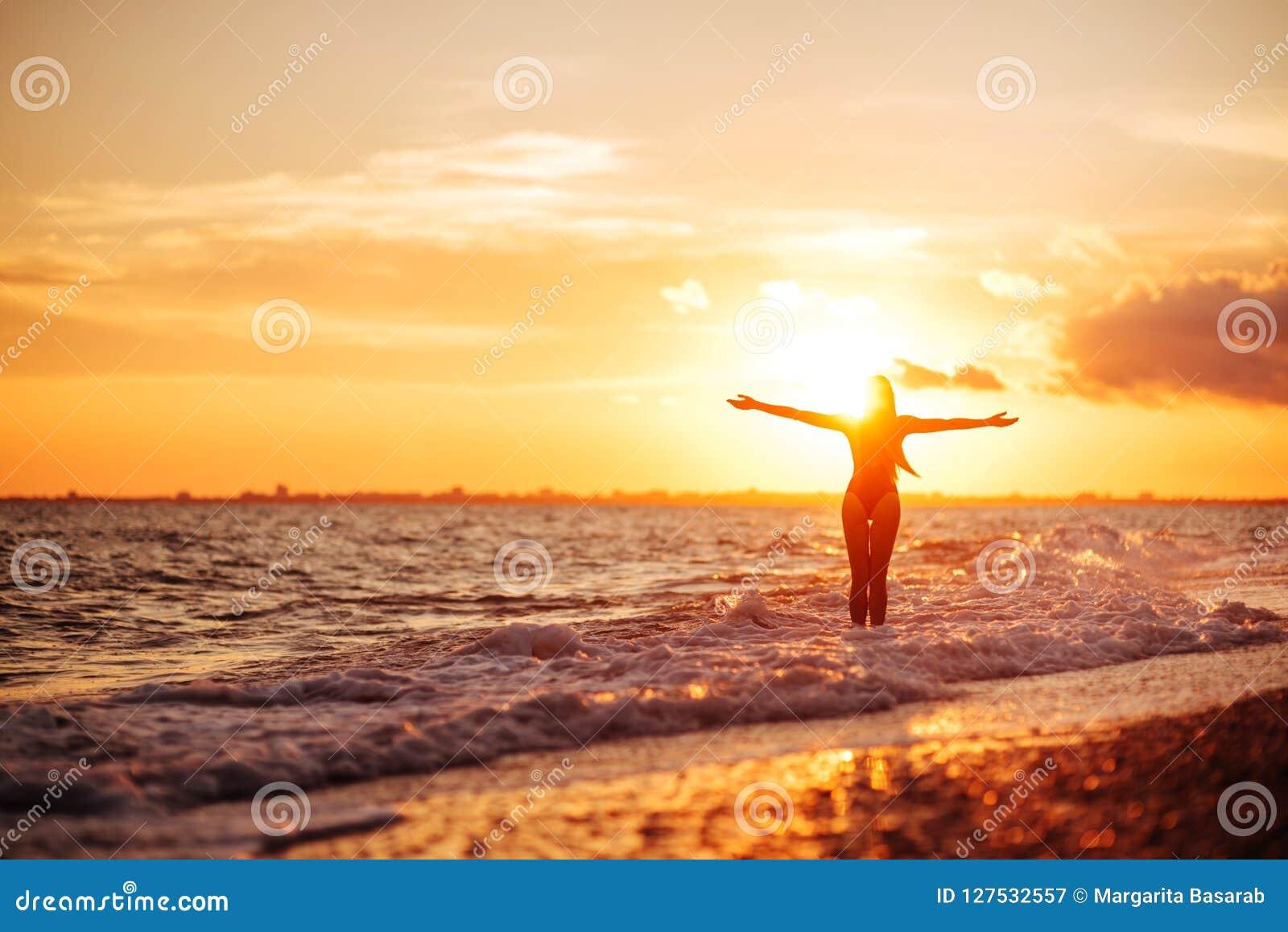 Onbezorgde vrouw die in de zonsondergang op het strand danst vakantie vitaliteit gezond het leven concept