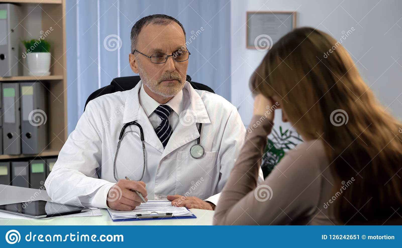 Oncologist informing woman about incurable disease, patient feels depressed