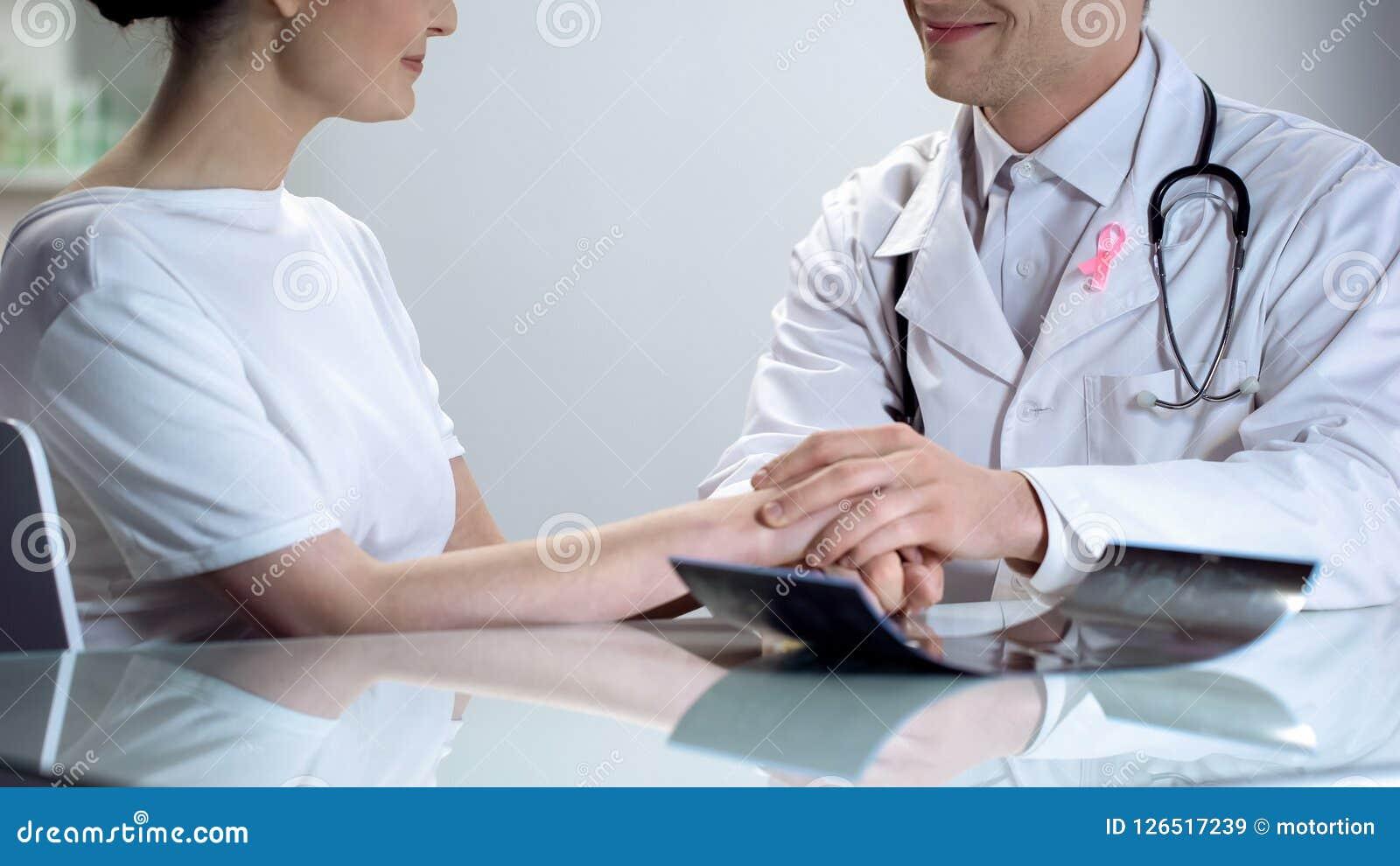 Oncologo che dice buone notizie della giovane signora, nessuna minaccia di cancro al seno entrambe che sorridono