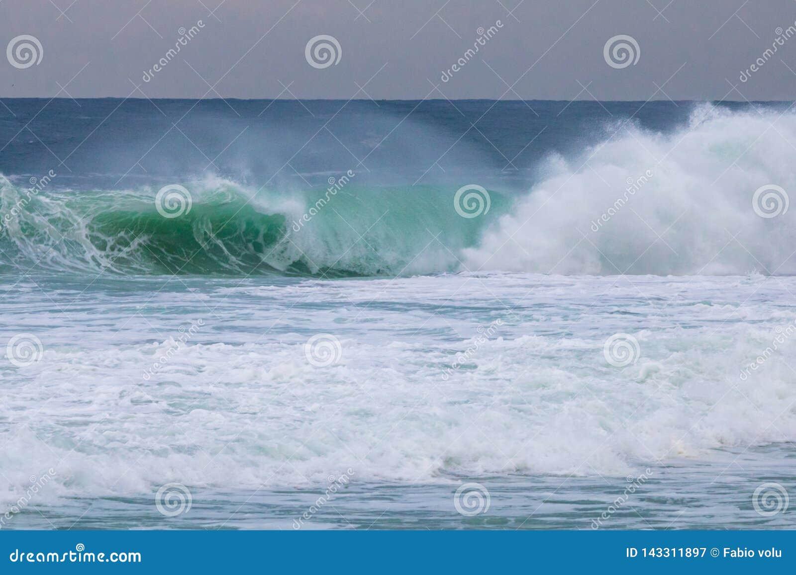 Onda azul e verde grande do mar tormentoso com o céu nebuloso em Barra da Tijuca Rio de janeiro Brazil Conceito da natureza climá