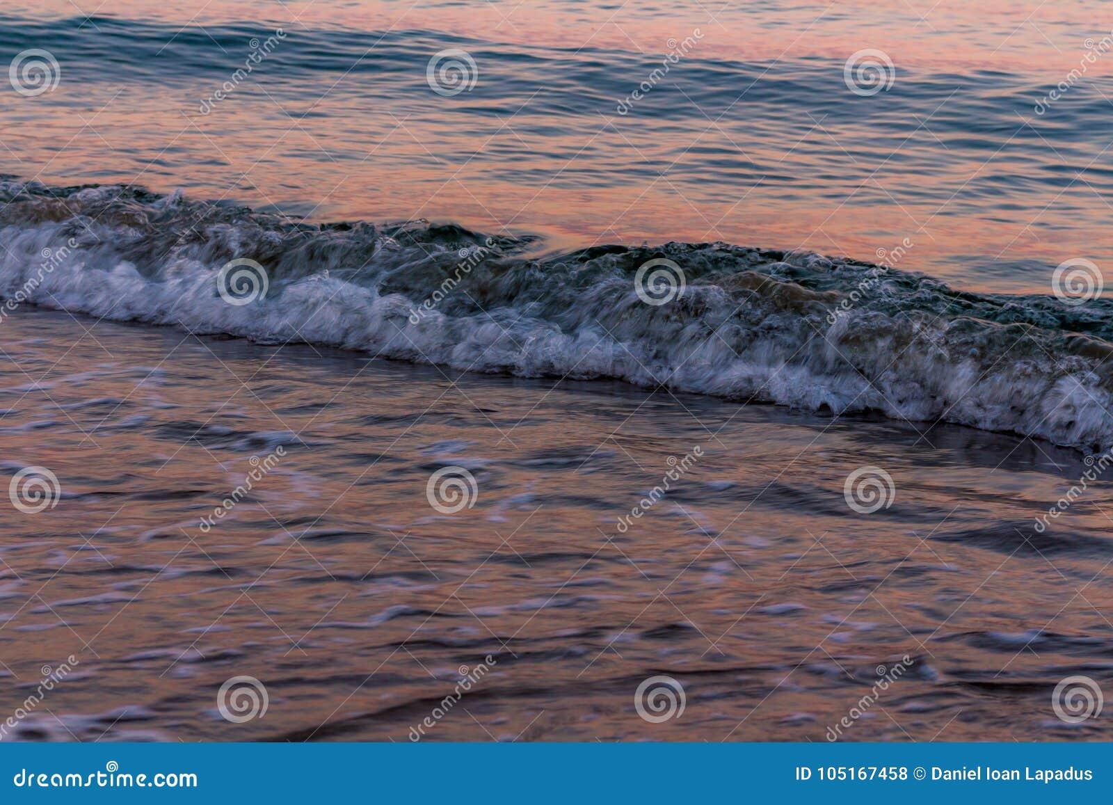Onda blured Cores do nascer do sol refletidas na água do mar