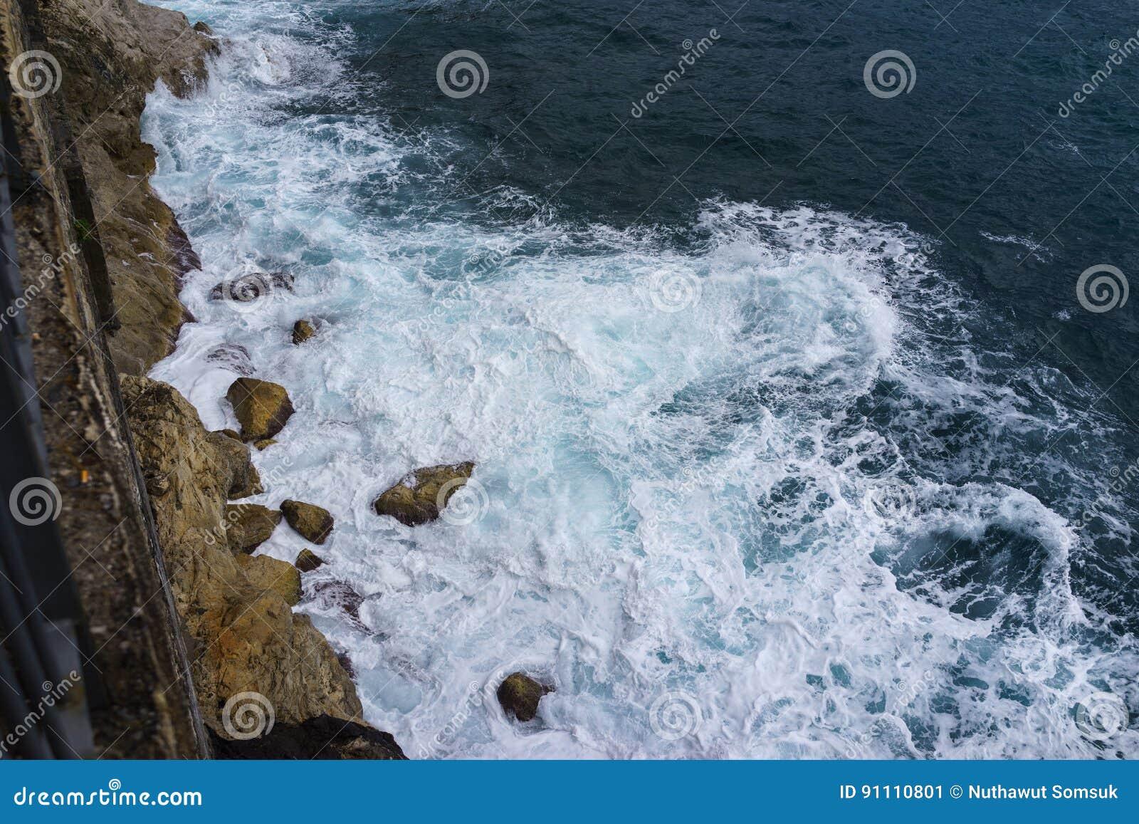 A onda de oceano bateu o penhasco na costa da rocha com pulverizador e espuma antes