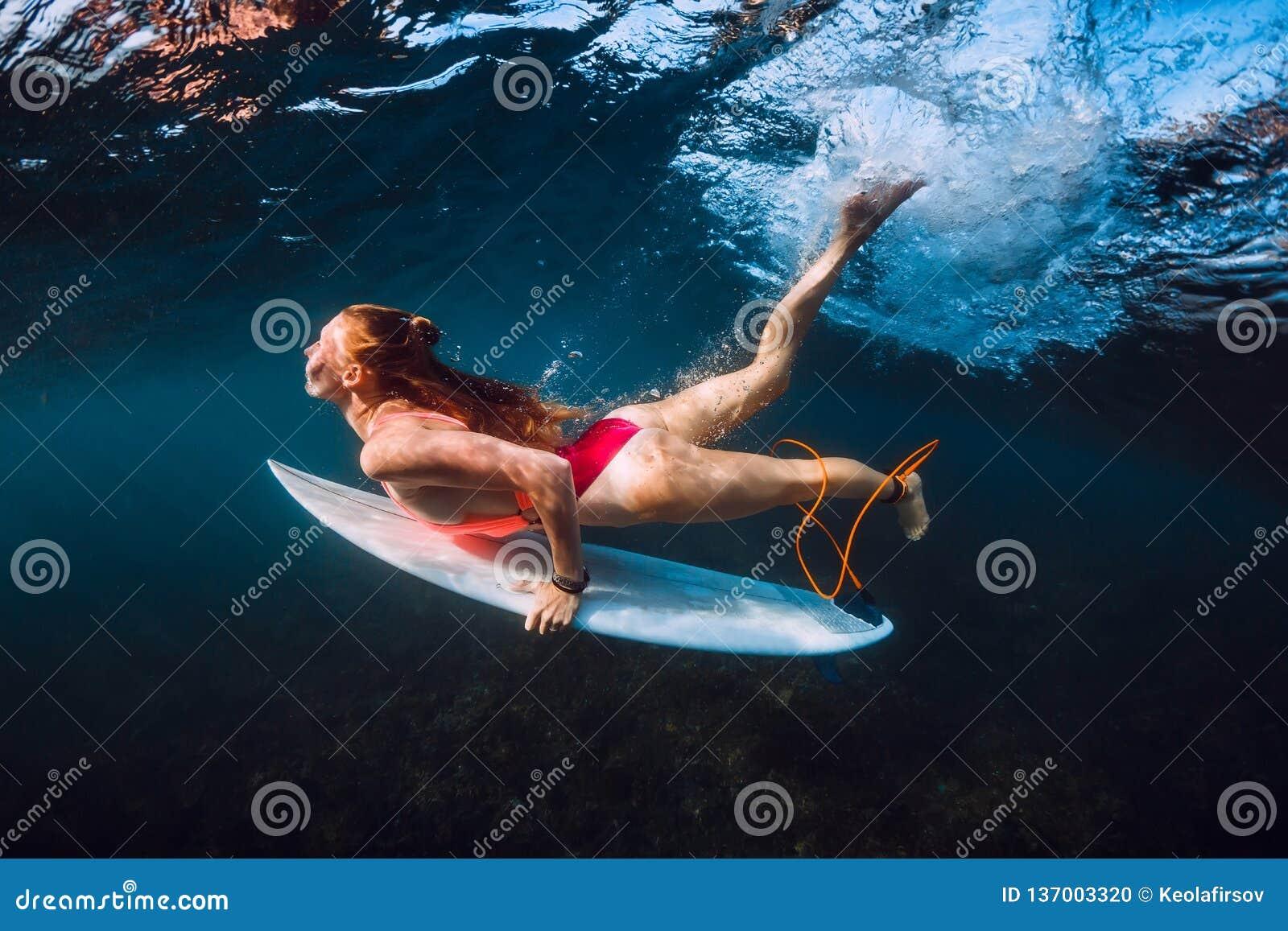 Onda subaquática do mergulho atrativo da mulher do surfista
