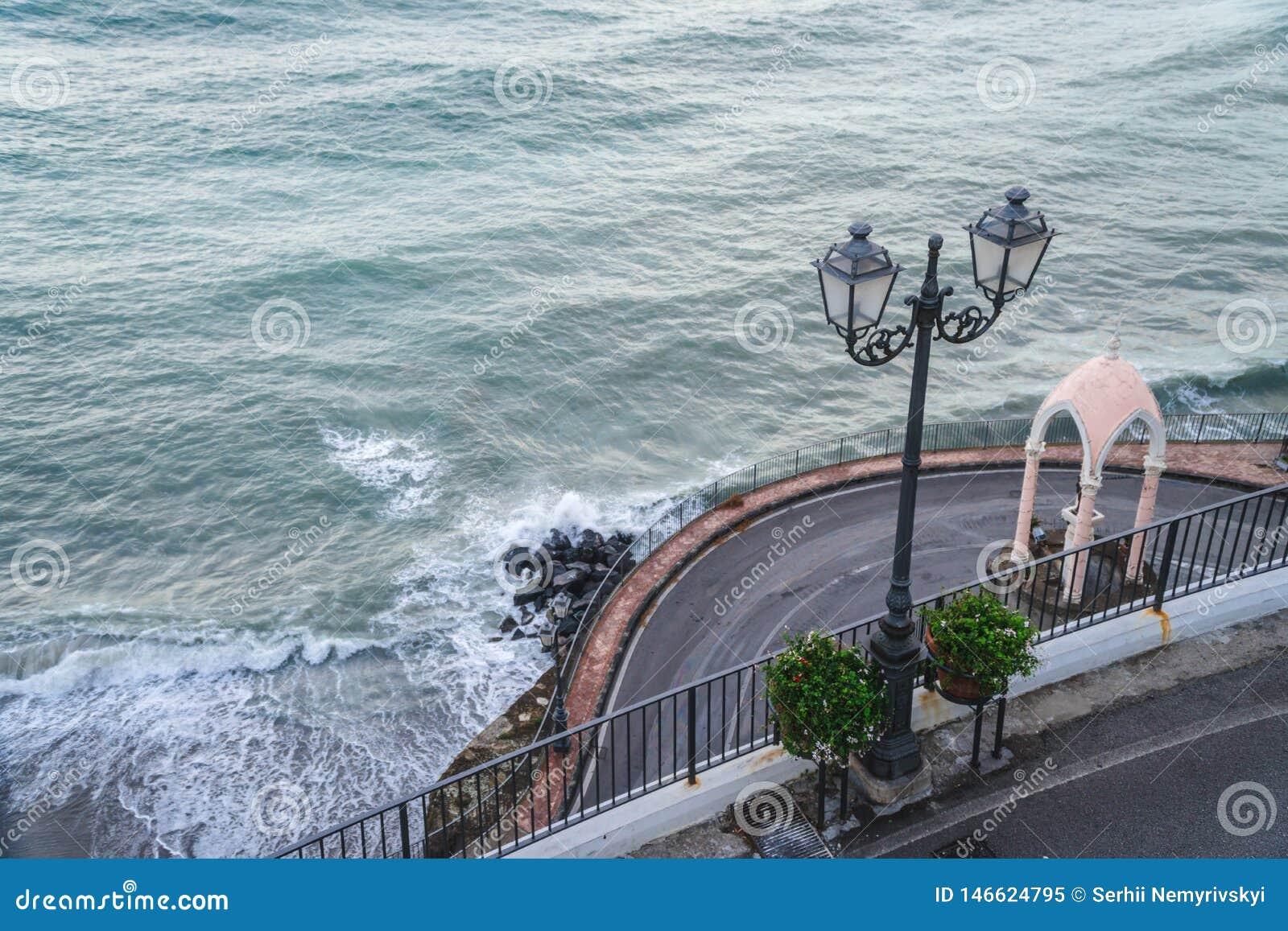 Ondas da praia das nuvens de tempestade do mar na baía de Sorrento do meta em Itália, fim da estação, tempo frio