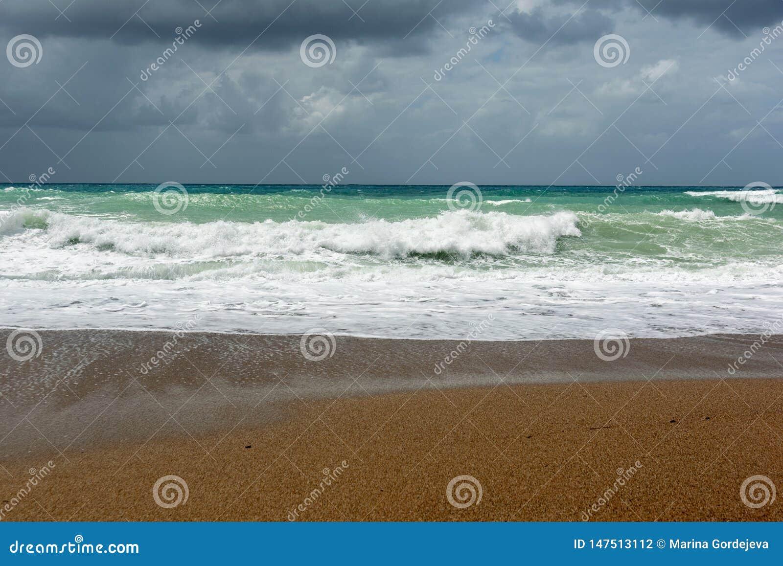 Ondas en la playa de la arena del Mar Egeo en Rodas