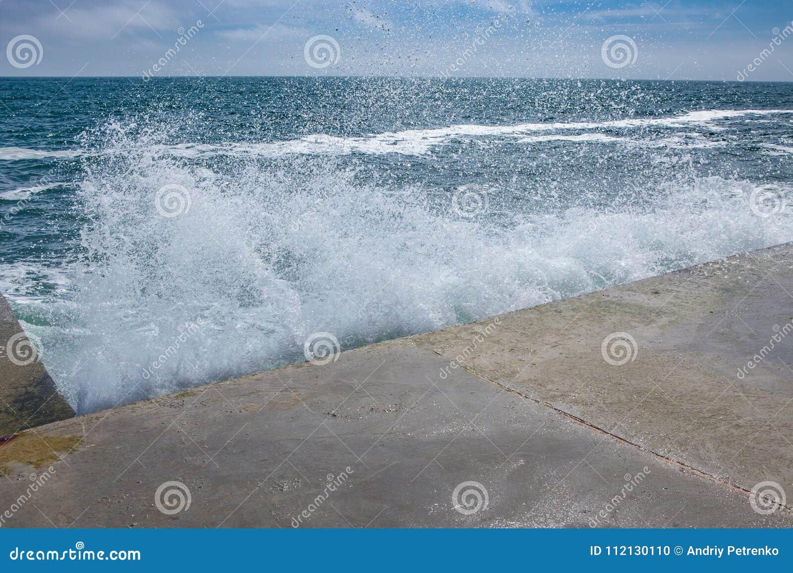 Ondas grandes en costa rocosa y el mar azul