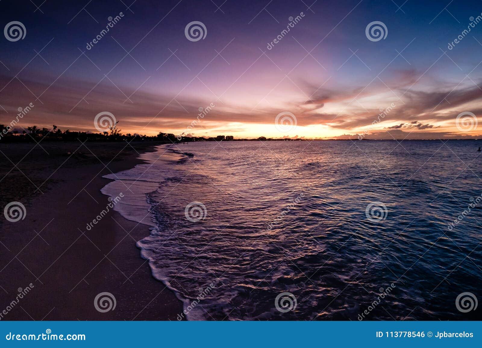 Ondas que se estrellan en la playa durante puesta del sol Púrpura anaranjada hermosa s