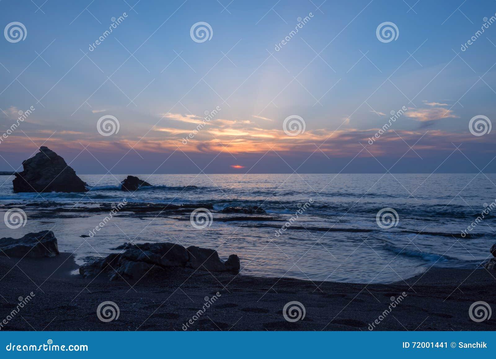 Onde che spruzzano vicino alla roccia sola, tramonto