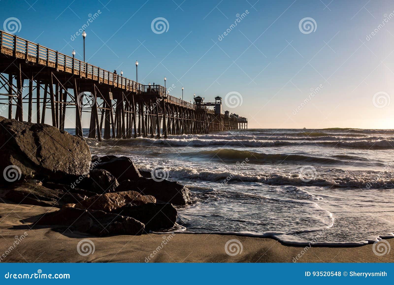 Onde e massi alla base del pilastro di pesca di riva dell oceano