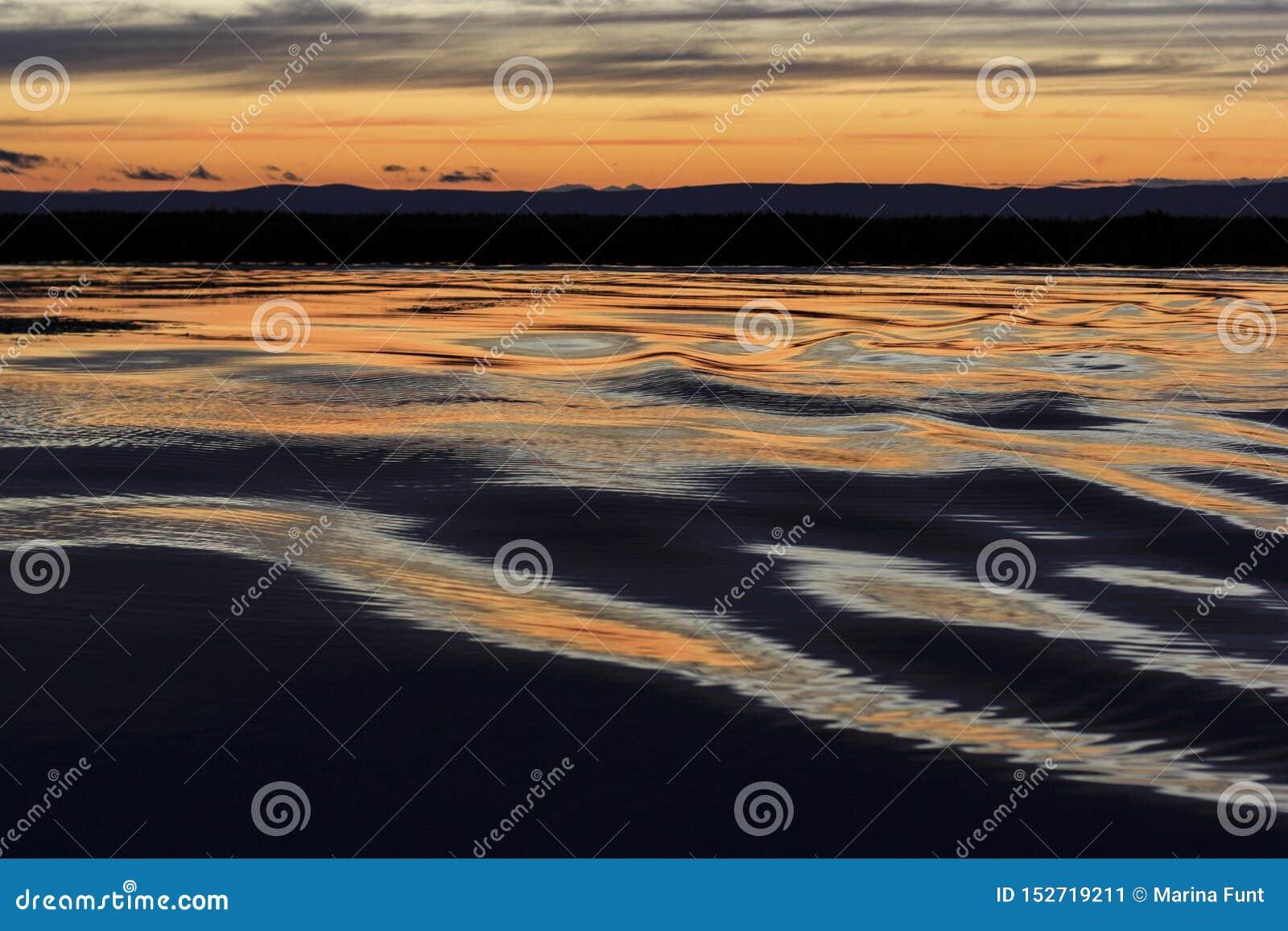 Onde sul lago al tramonto