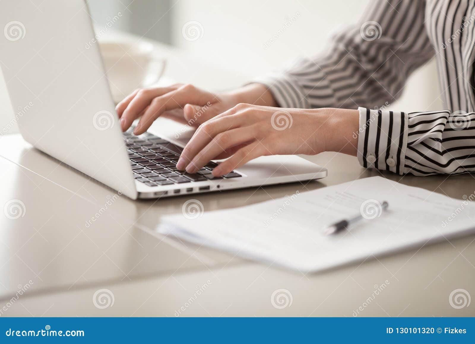 Onderneemster die aan laptop, vrouwelijke handen werken die op toetsenbord typen