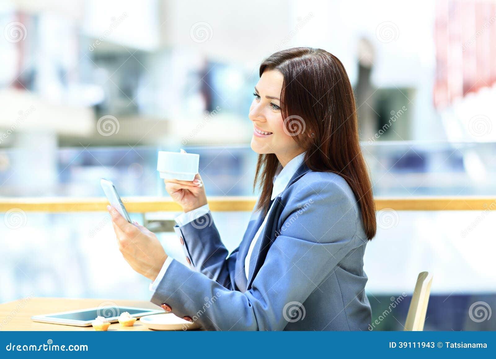 Onderneemster die een kop van koffie hebben terwijl het lezen