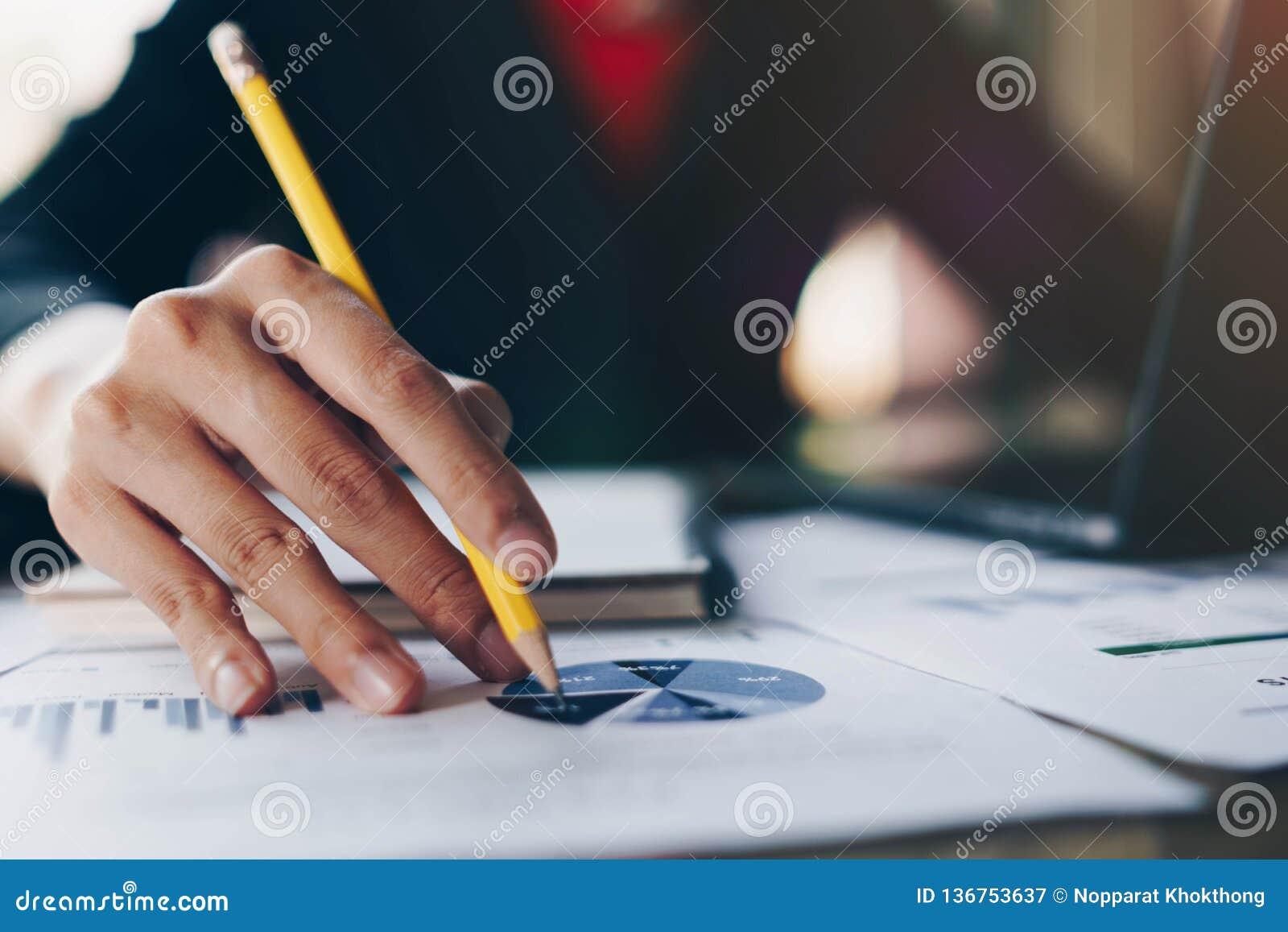 Onderneemster die gegevens van rapport en laptop computer over houten lijst analyseren Het concept van financiën