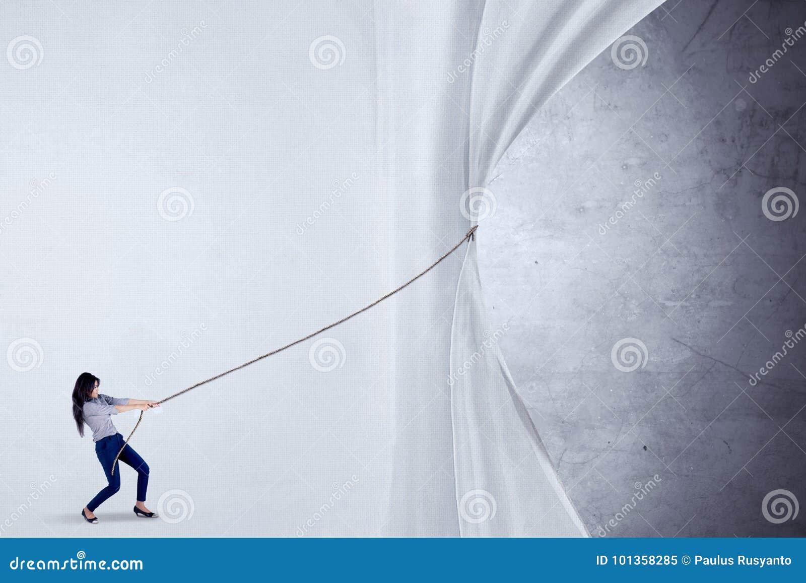 Onderneemster die gordijn met kabel trekken