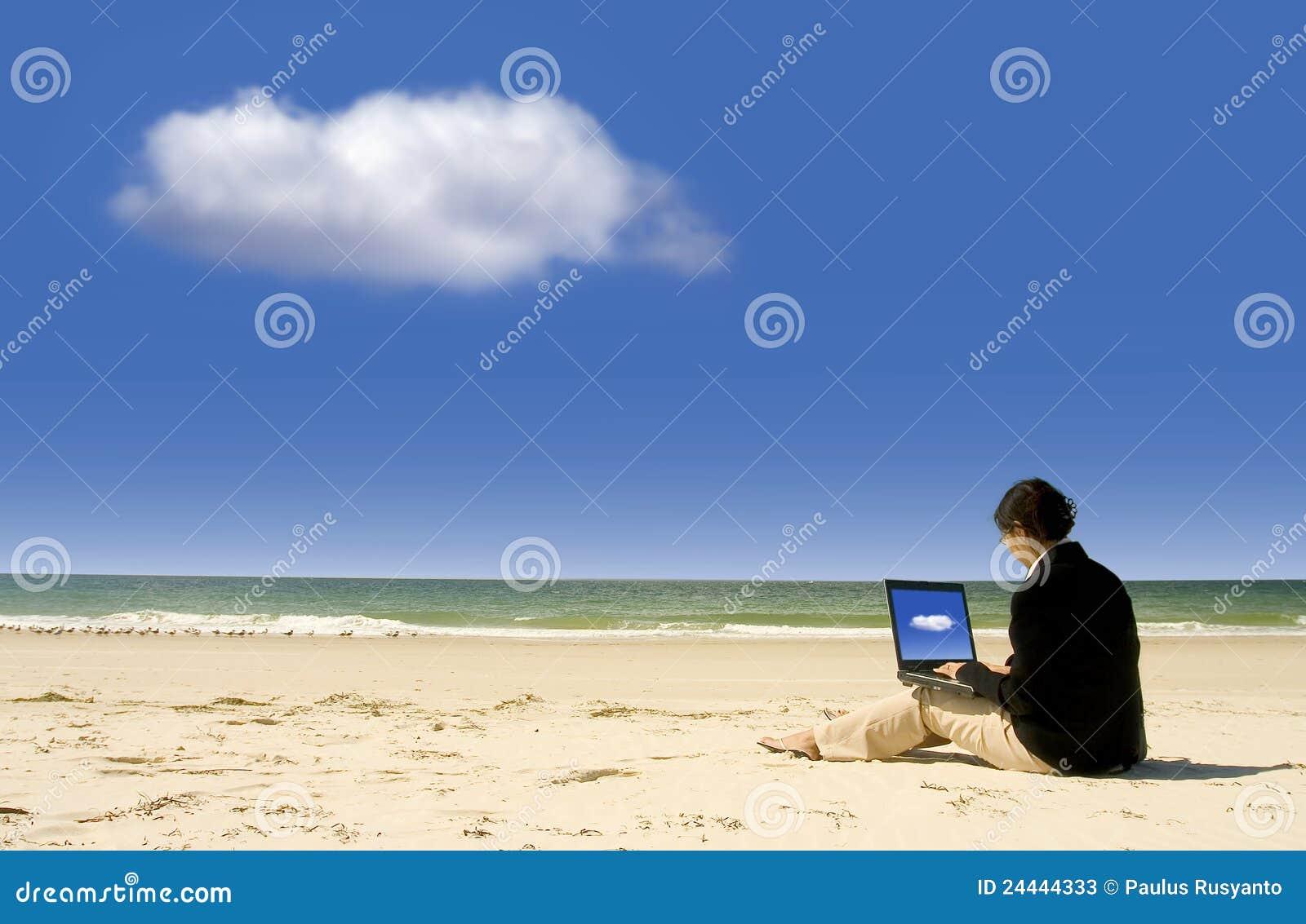 Onderneemster die met laptop bij strand werkt