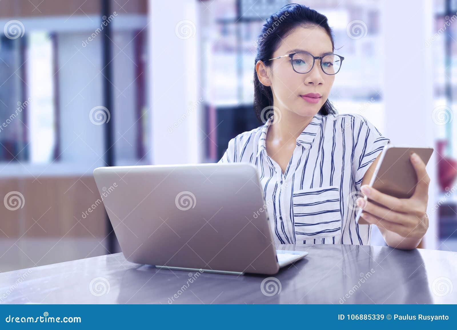 Onderneemster die met mobiele telefoon en laptop werken