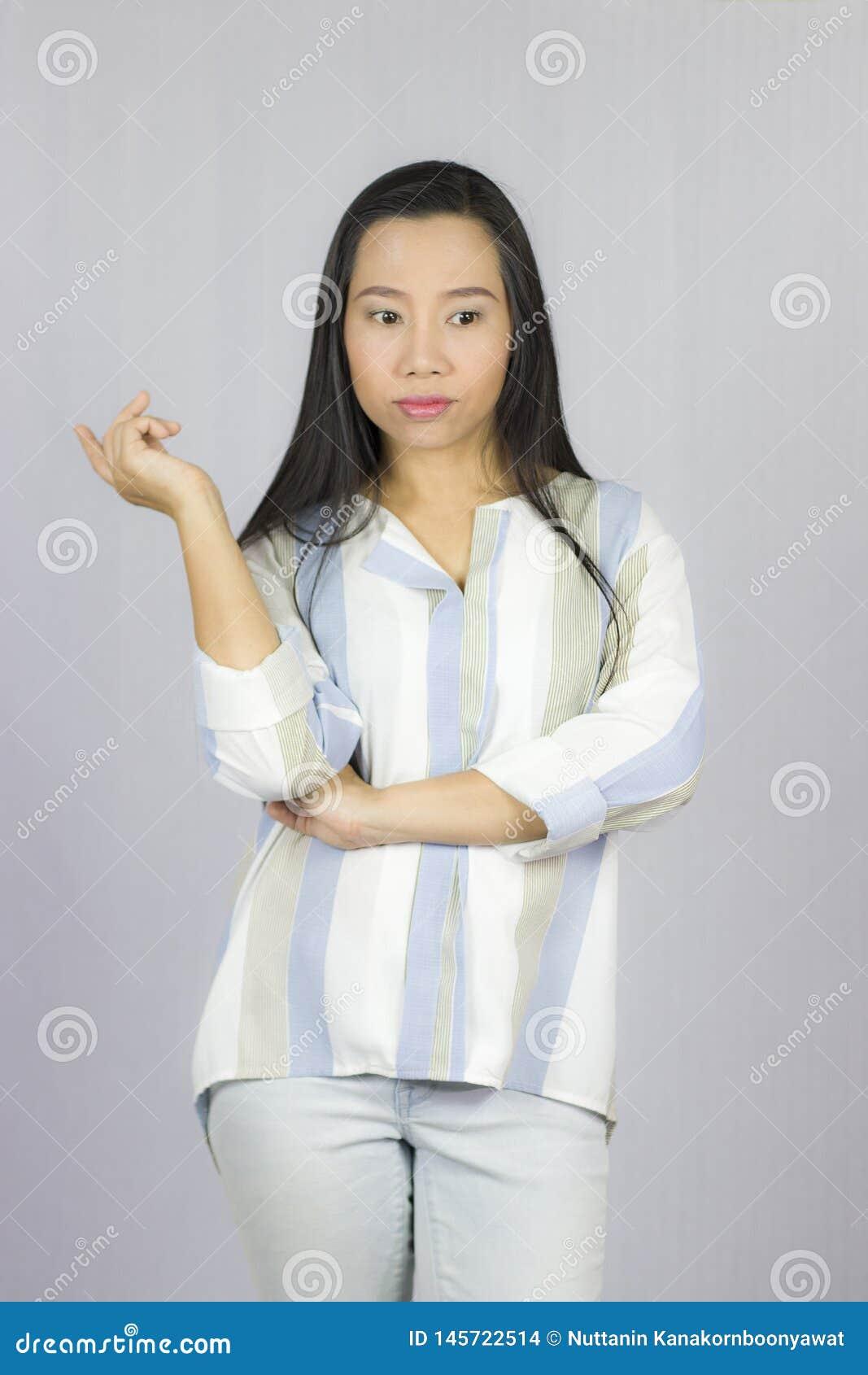 Onderneemster die overhemds stellende glimlach draagt denkt die die op grijze achtergrond wordt ge?soleerd