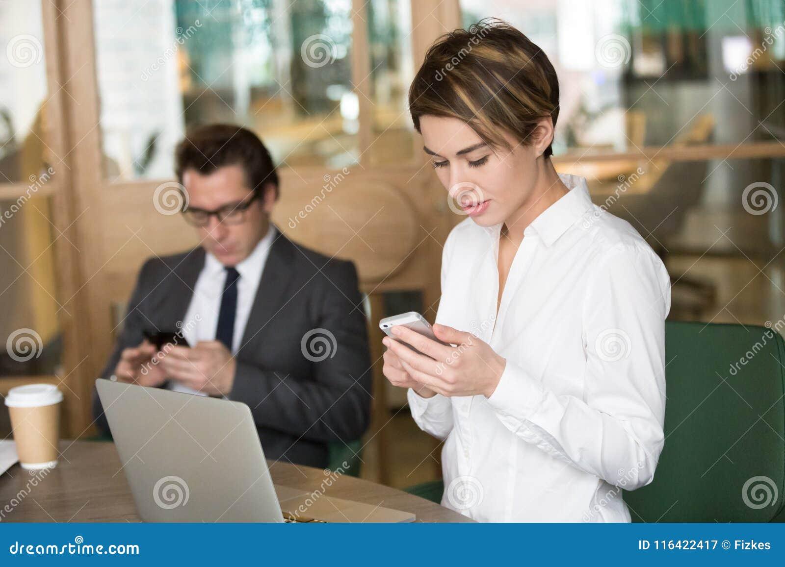 Onderneemster en zakenman die mobiele telefoons voor het werk binnen met behulp van van