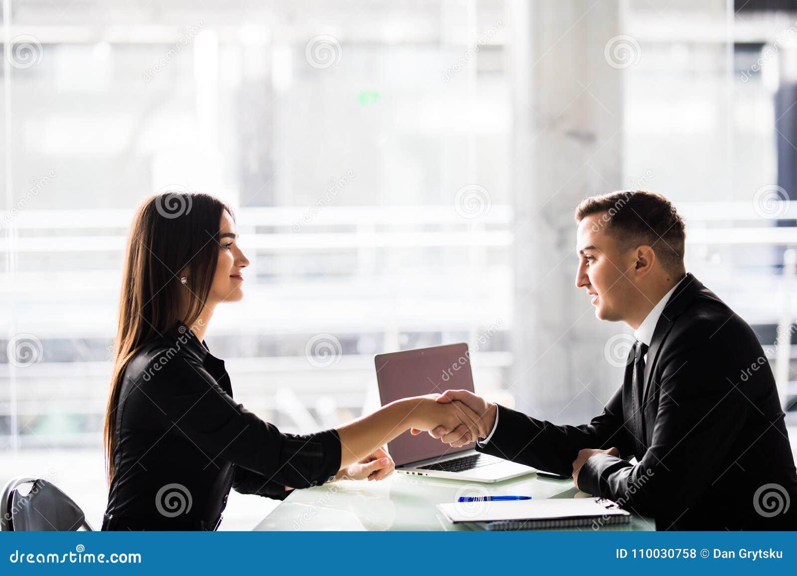 Onderneemster en zakenman het schudden overhandigt de lijst met laptop en documenten op het kantoor, prettige commerciële vergade