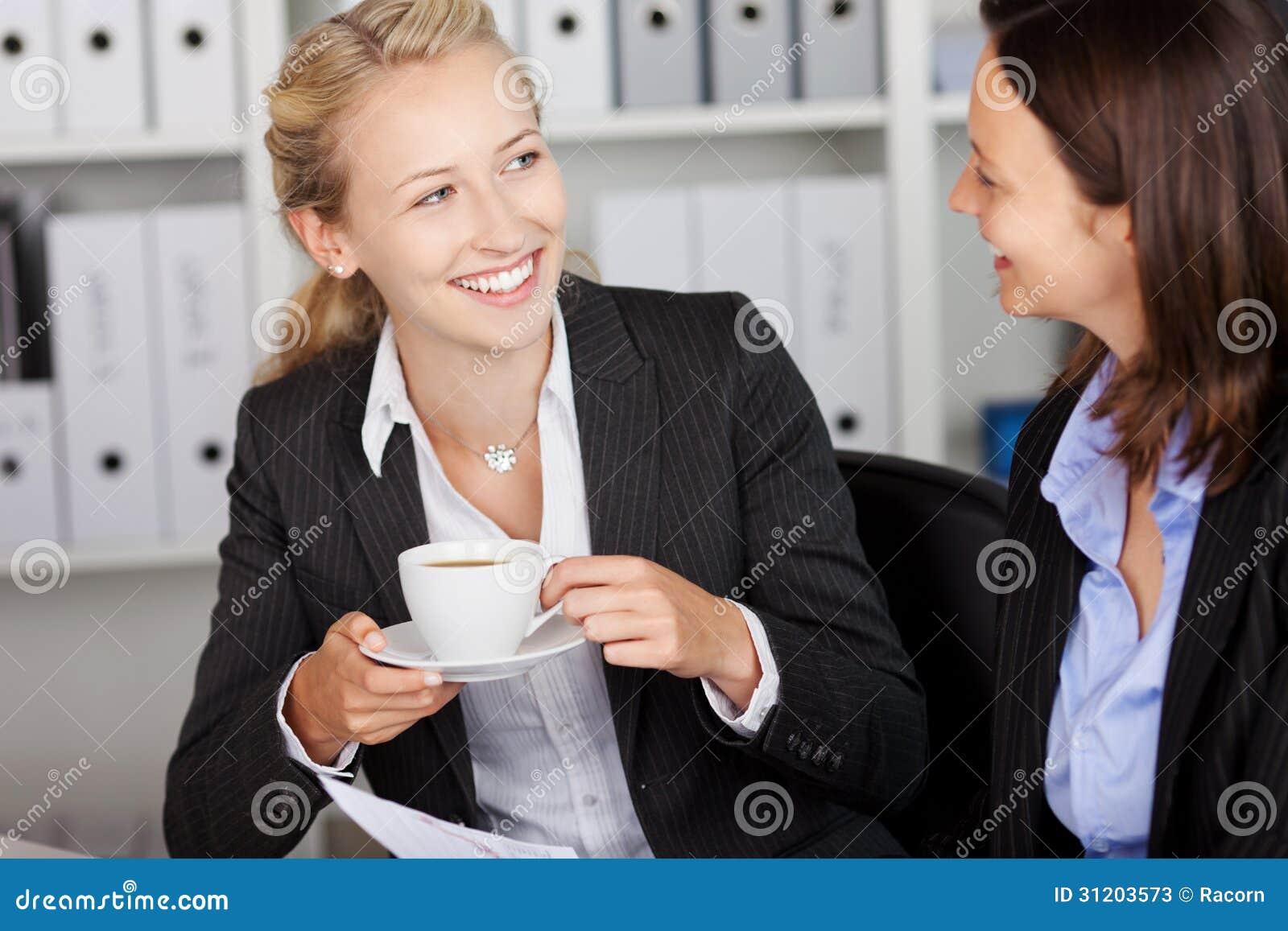 Onderneemster Having Coffee While die Medewerker bekijken