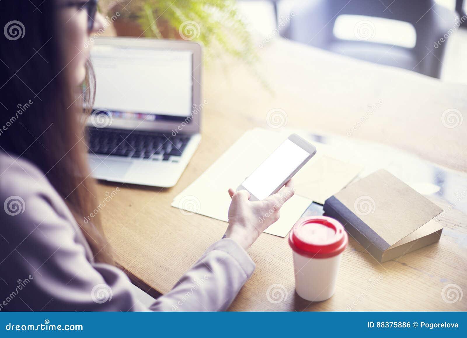 Onderneemster het gebruiken telefoneert en laptop terwijl het zitten in zijn modern zolderbureau Concept jongeren die mobiele app